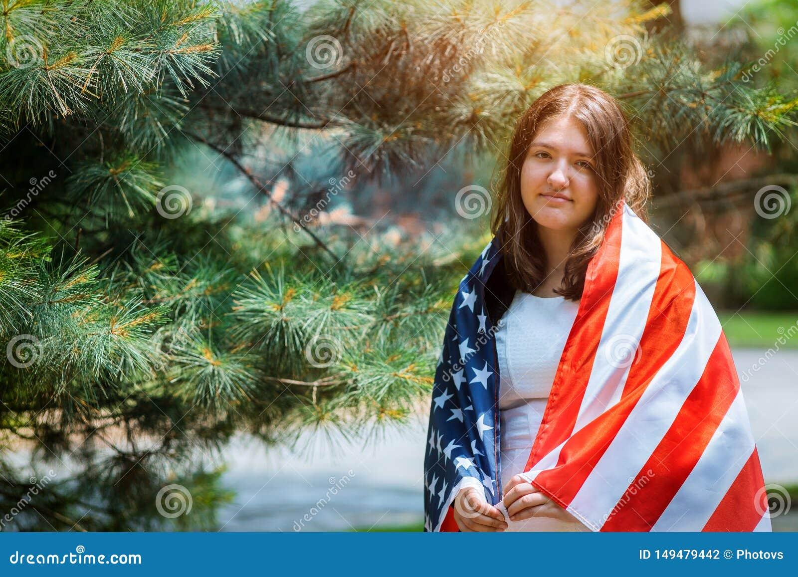 Jeune fille avec la robe classique tenant le drapeau am?ricain pendant le Jour de la D?claration d Ind?pendance de parc