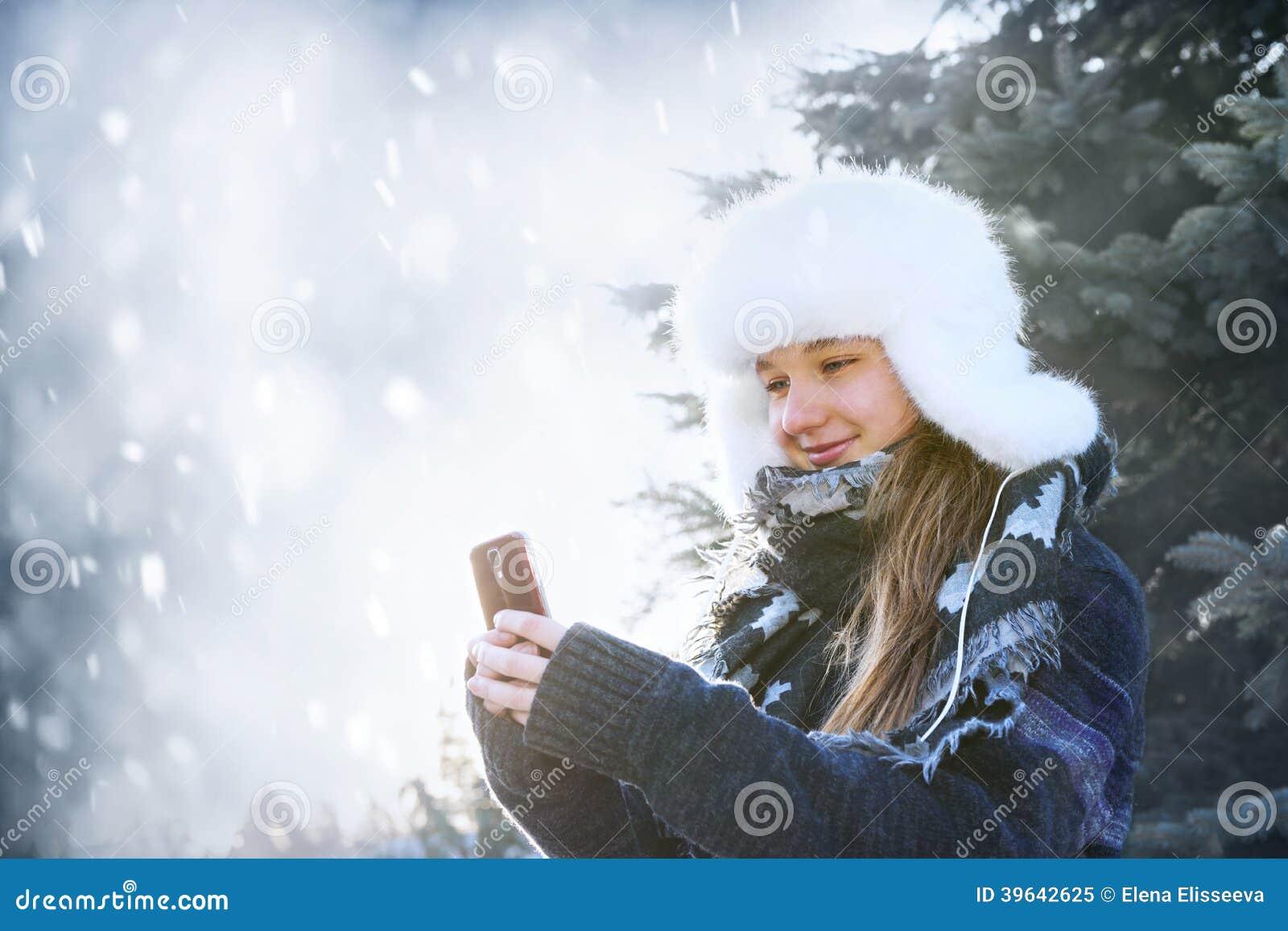 Jeune fille avec le téléphone portable en hiver