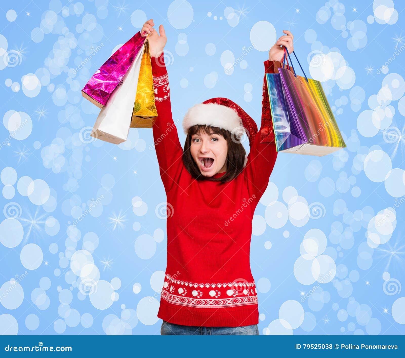 Jeune fille avec un chapeau de Santa de Noël sur sa tête, tenant le shopp