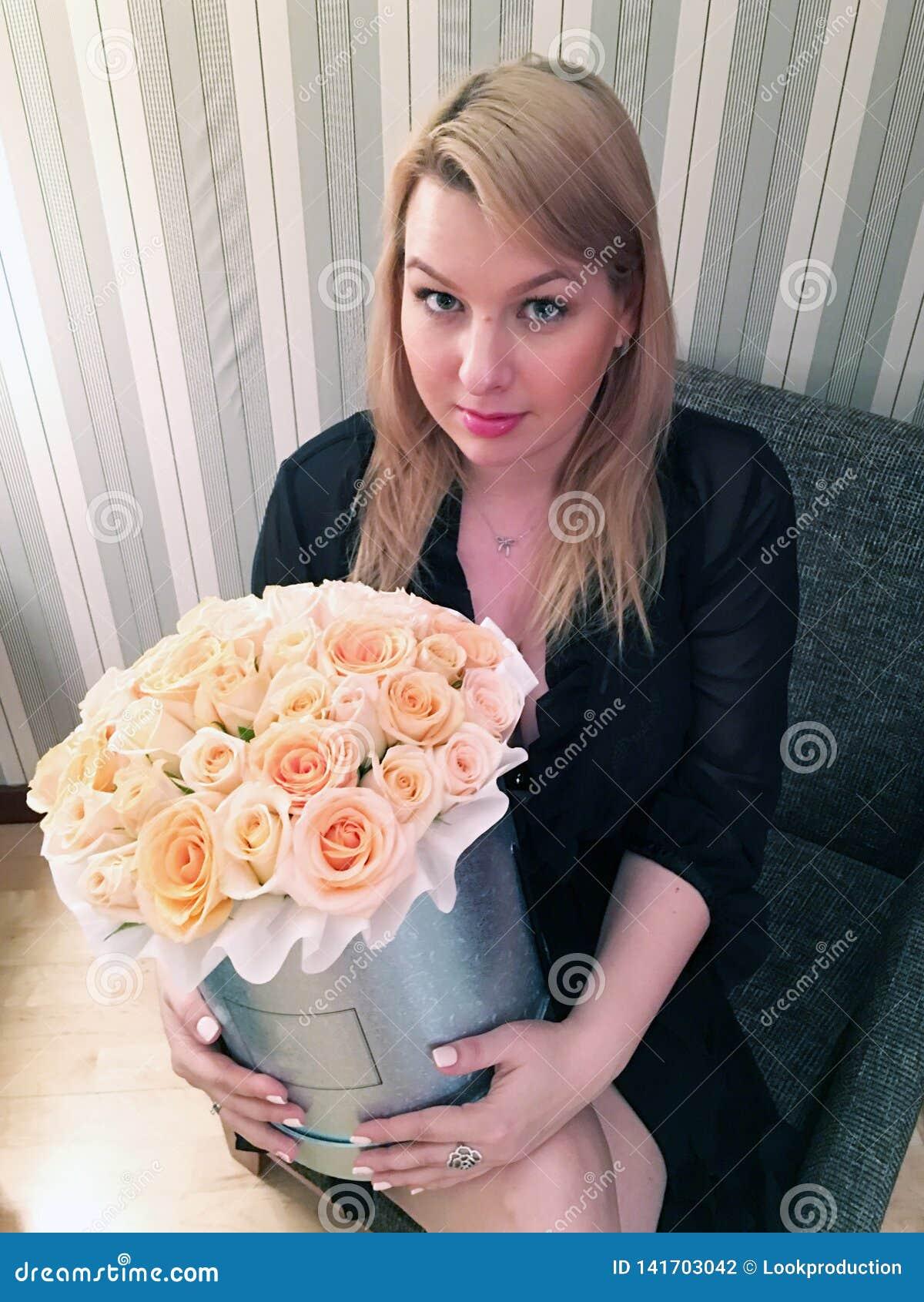 Jeune fille blonde sexy dans la chambre avec le grand bouquet de boîte des fleurs de roses