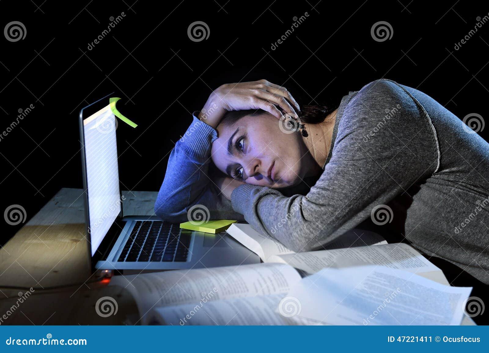 Jeune fille désespérée d étudiant dans l effort pour l examen étudiant avec les livres et l ordinateur portable d ordinateur tard