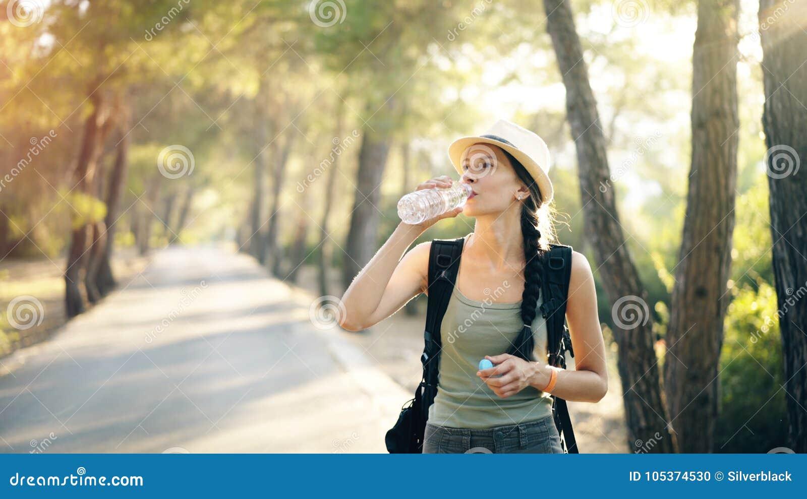 Jeune fille de touristes attirante régénérant par l eau potable après voyage de randonneur