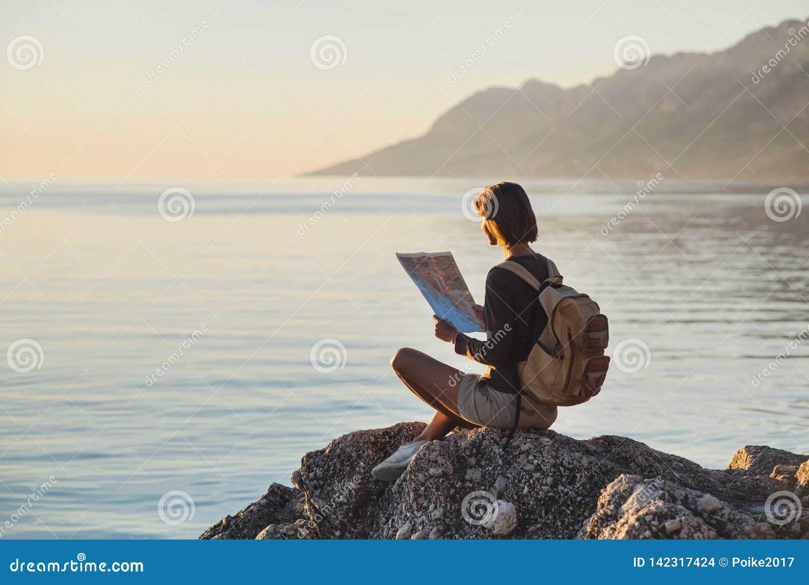 Jeune fille de voyageur s asseyant avec la carte près de la mer au coucher du soleil, au voyage, à la hausse et au concept actif