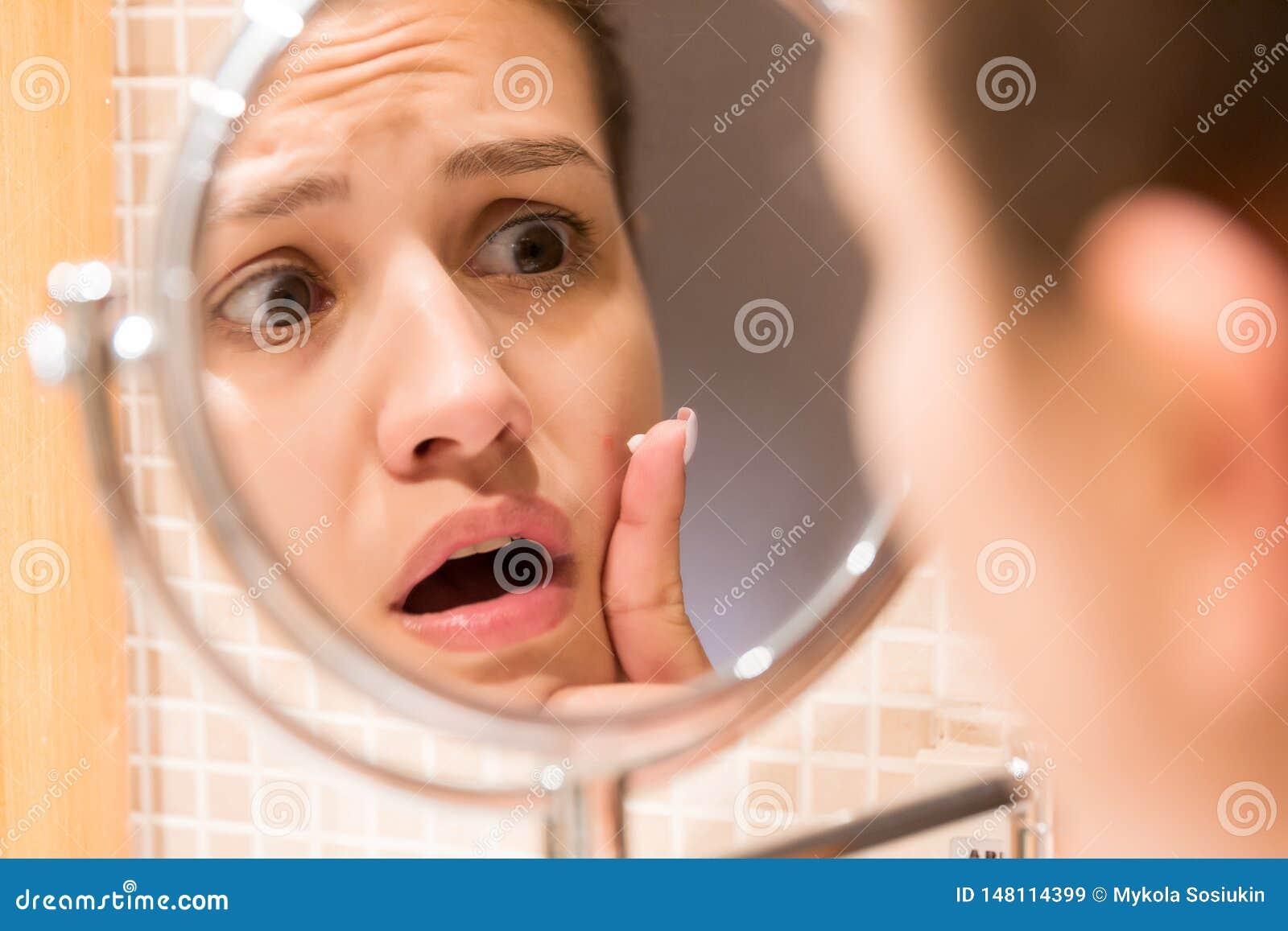 Jeune fille devant un miroir de salle de bains mettant la cr?me sur un bouton rouge Soins de la peau de beaut? et concept de mati