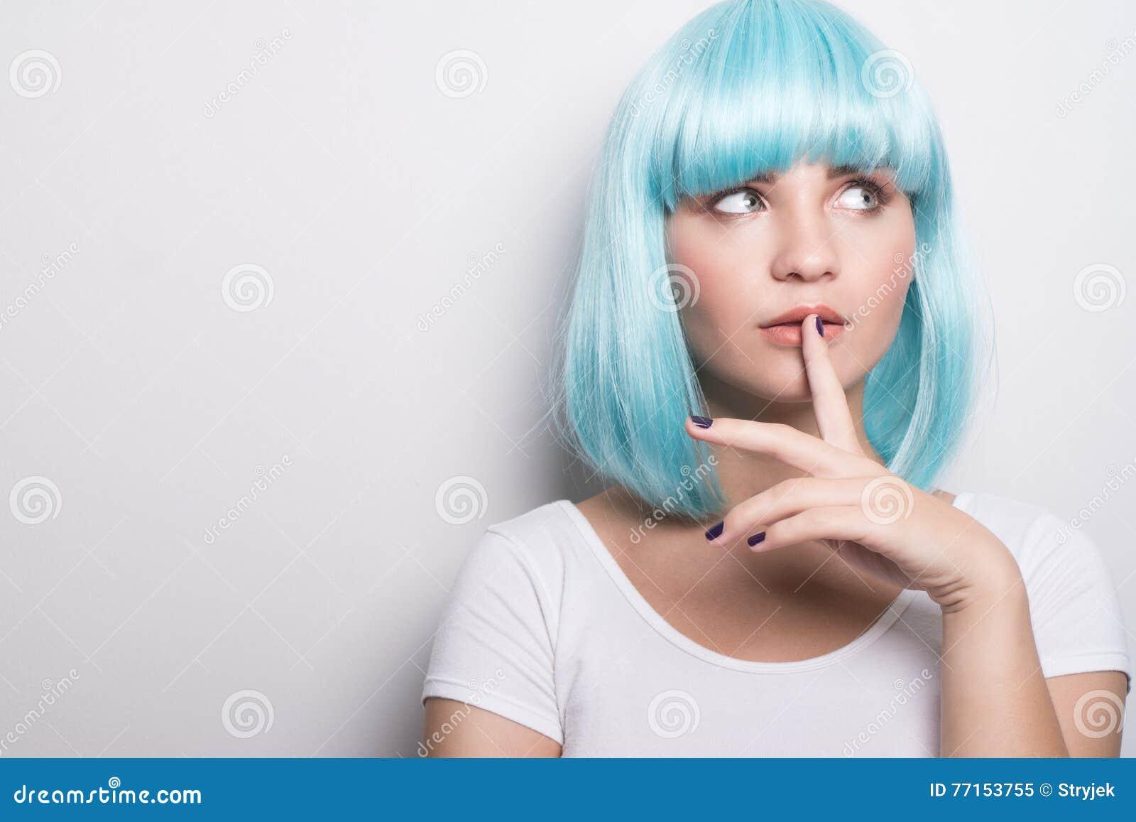 Jeune fille effrontée dans le style futuriste moderne avec la perruque bleue pensant au-dessus du blanc