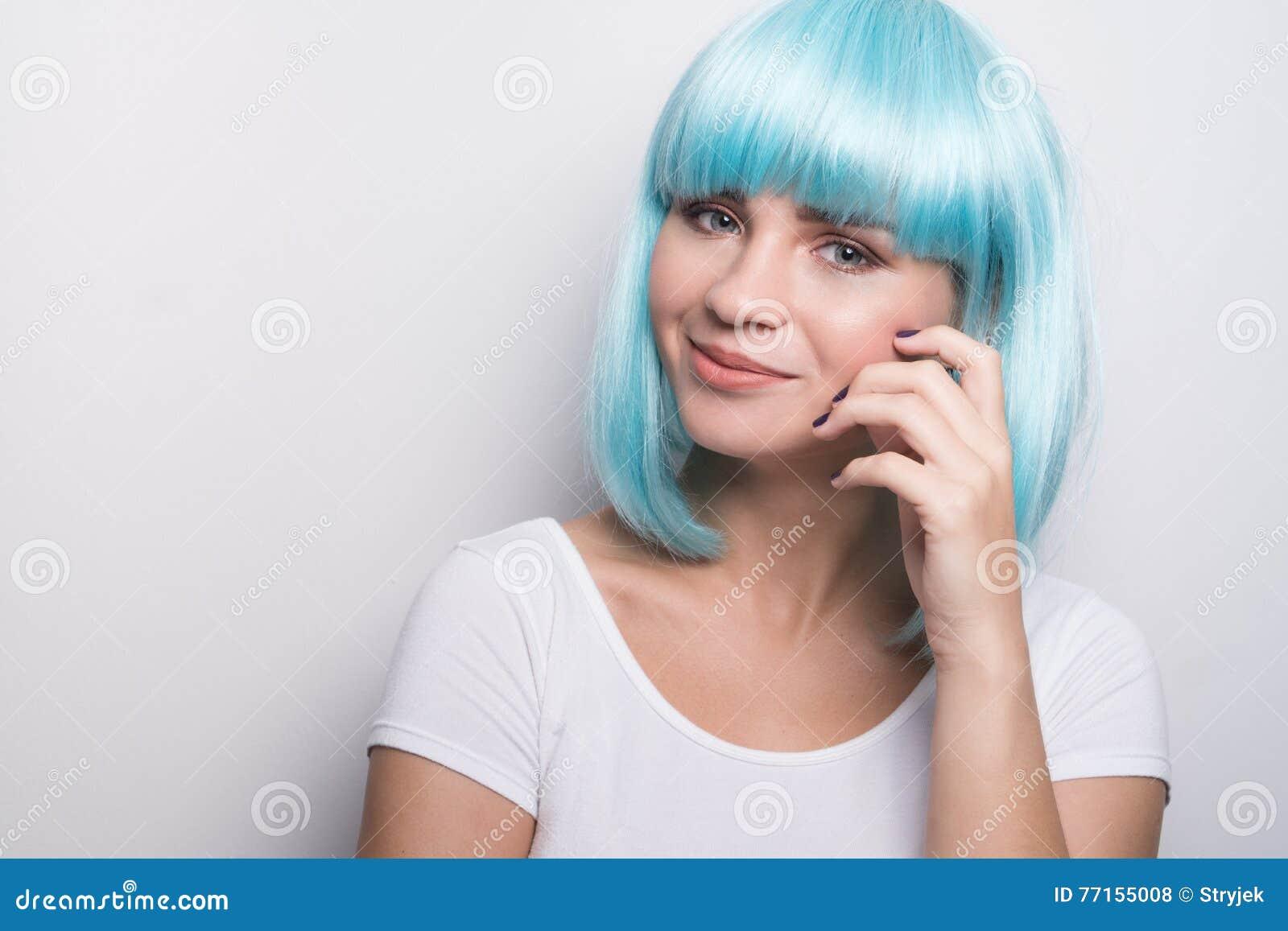 Jeune fille effrontée dans le style futuriste moderne avec la perruque bleue posant au-dessus du blanc