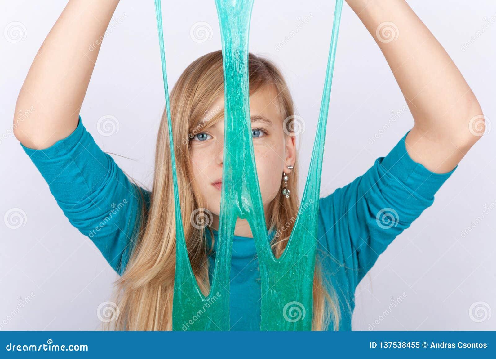 Jeune fille jouant avec la boue le tenant devant son visage