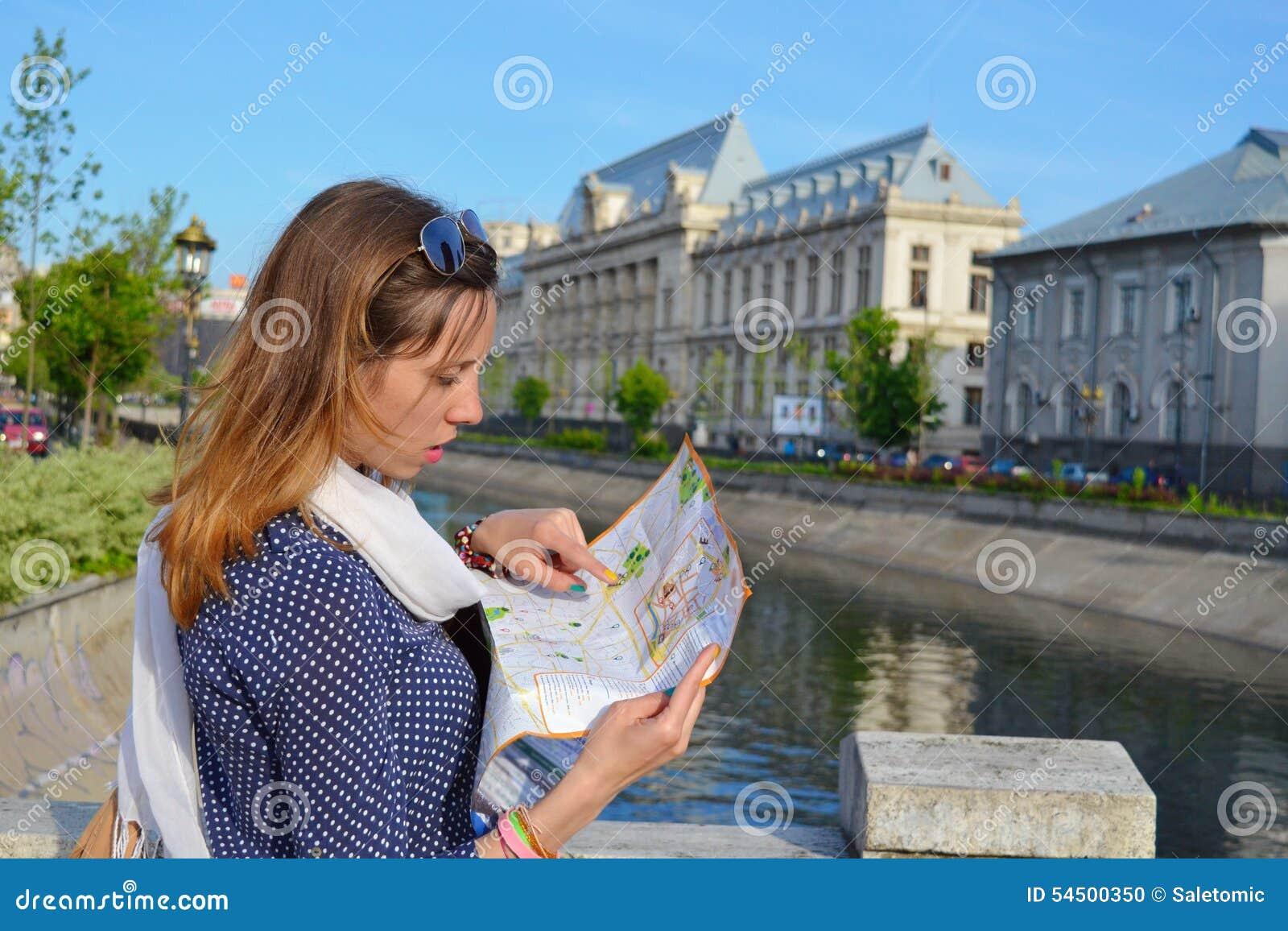 Jeune fille lisant une carte près d une rivière