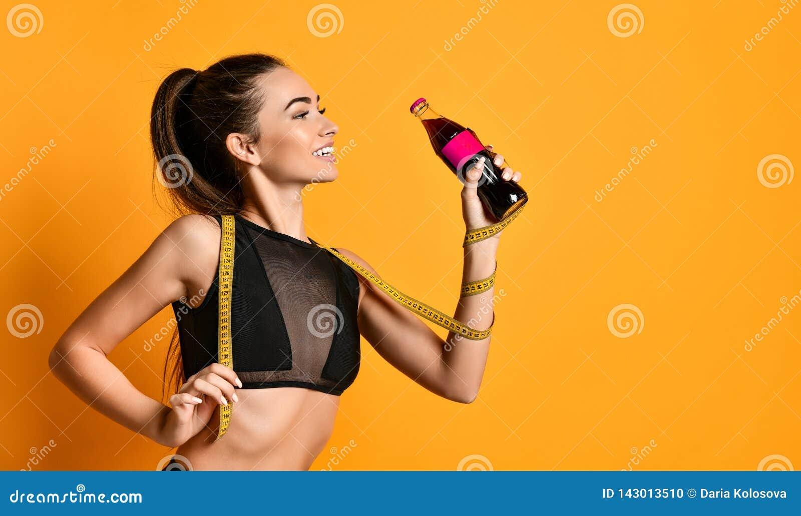 Jeune fille mignonne de forme physique dans des regards noirs de costume dans la caméra et maintenir la bande et la bouteille de