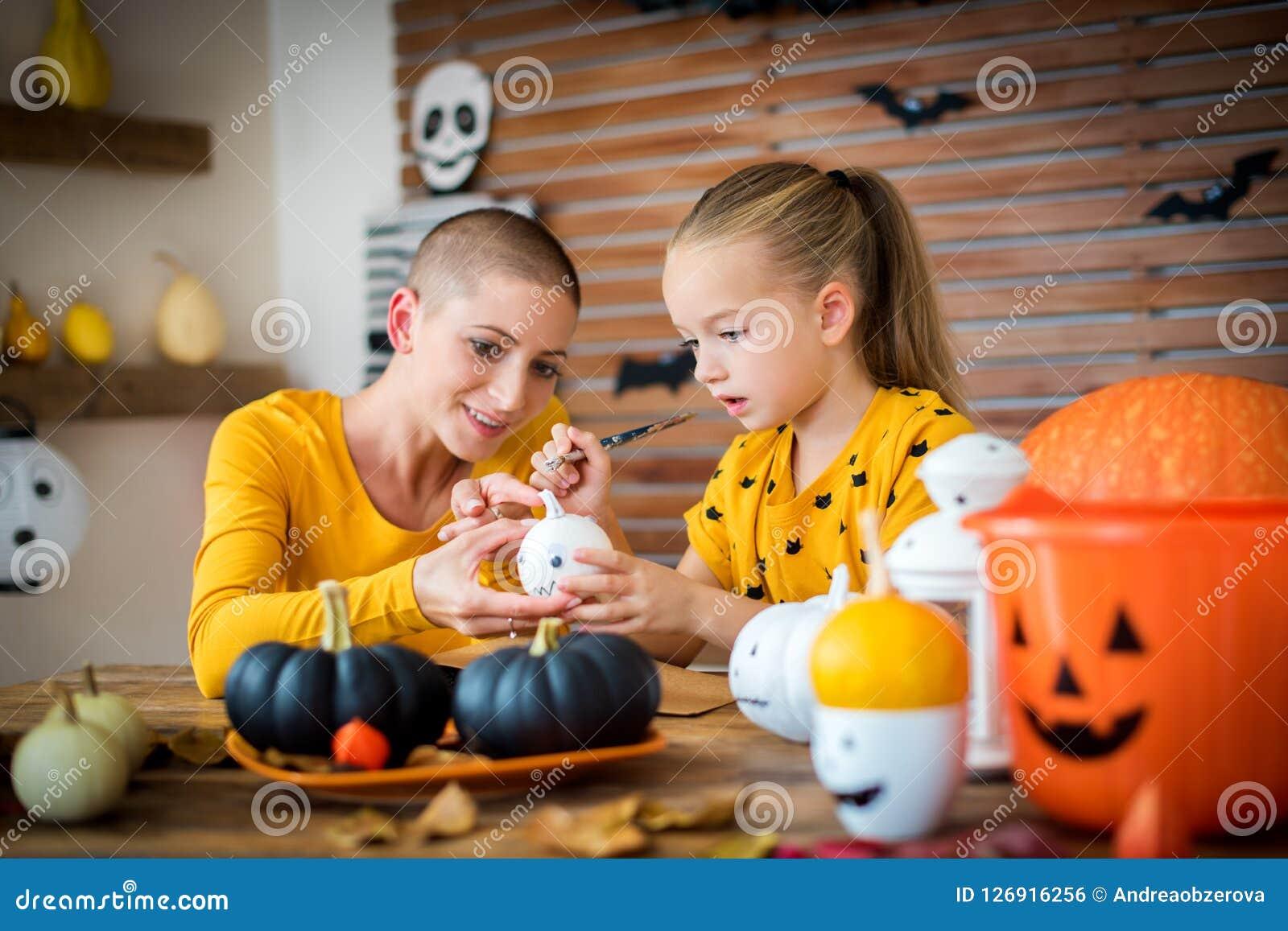 Jeune fille mignonne s asseyant à une table, décorant de petits potirons blancs avec sa mère, un cancéreux DIY Halloween