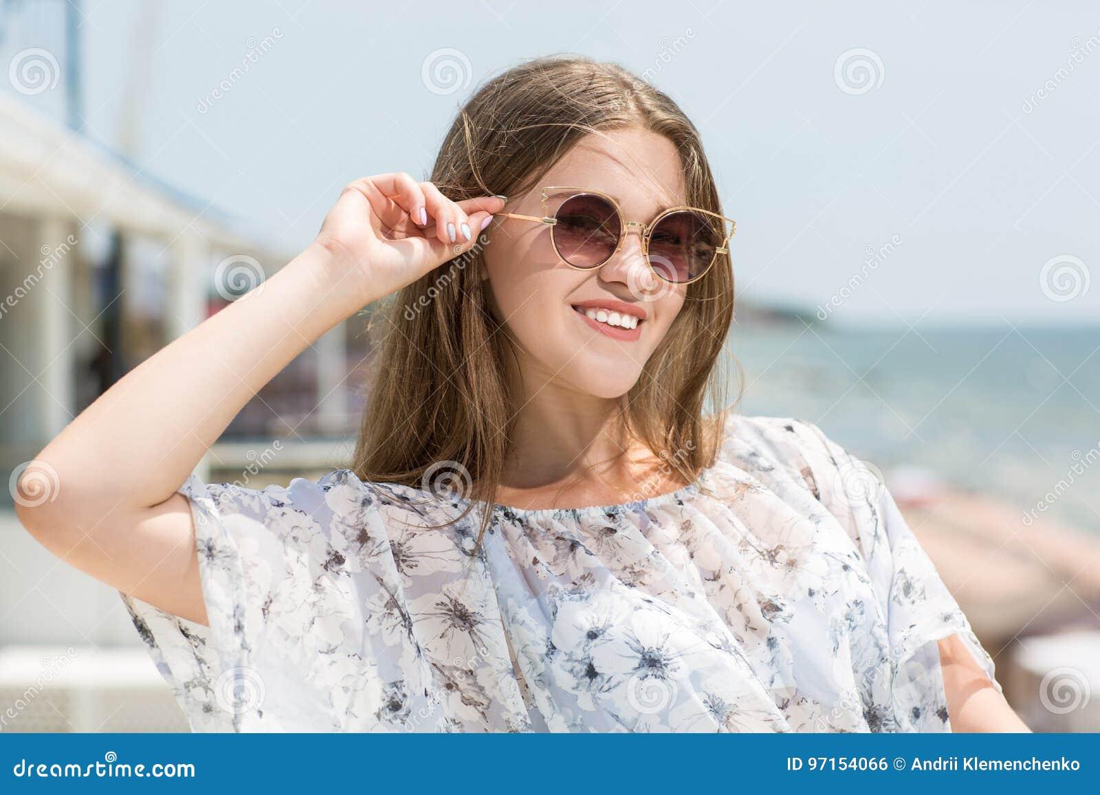 Jeune fille modèle avec du charme et belle en verres de soleil sur le fond de mer Un modèle femelle mignon Belle fille en glaces
