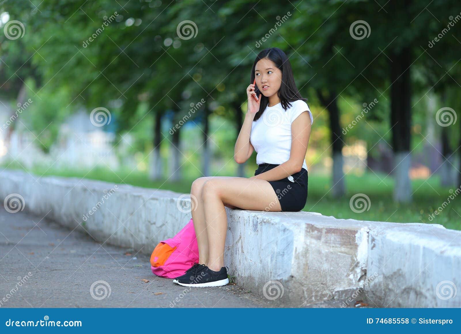 Jeune fille s asseyant et parlant au téléphone en parc