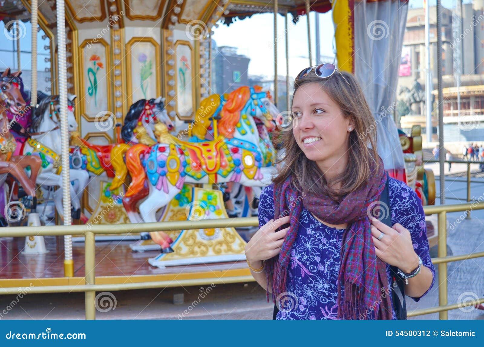 Jeune fille se tenant devant un carrousel