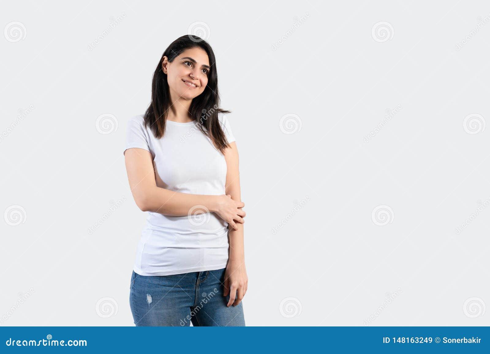 Jeune fille utilisant le T-shirt et les blues-jean blancs vides Fond gris de mur