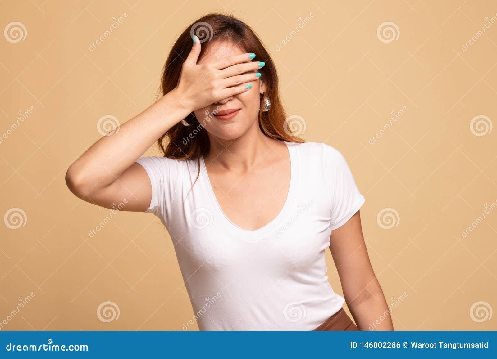 Jeune fin asiatique de femme ses yeux avec la main