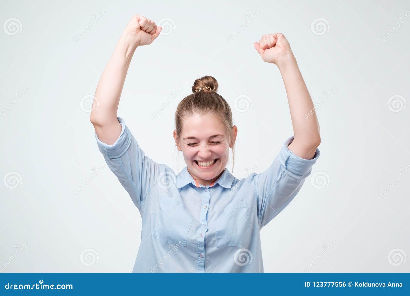 Jeune gagnant féminin réussi fort européen dans la chemise bleue soulevant des bras hurlant avec la joie et l excitation