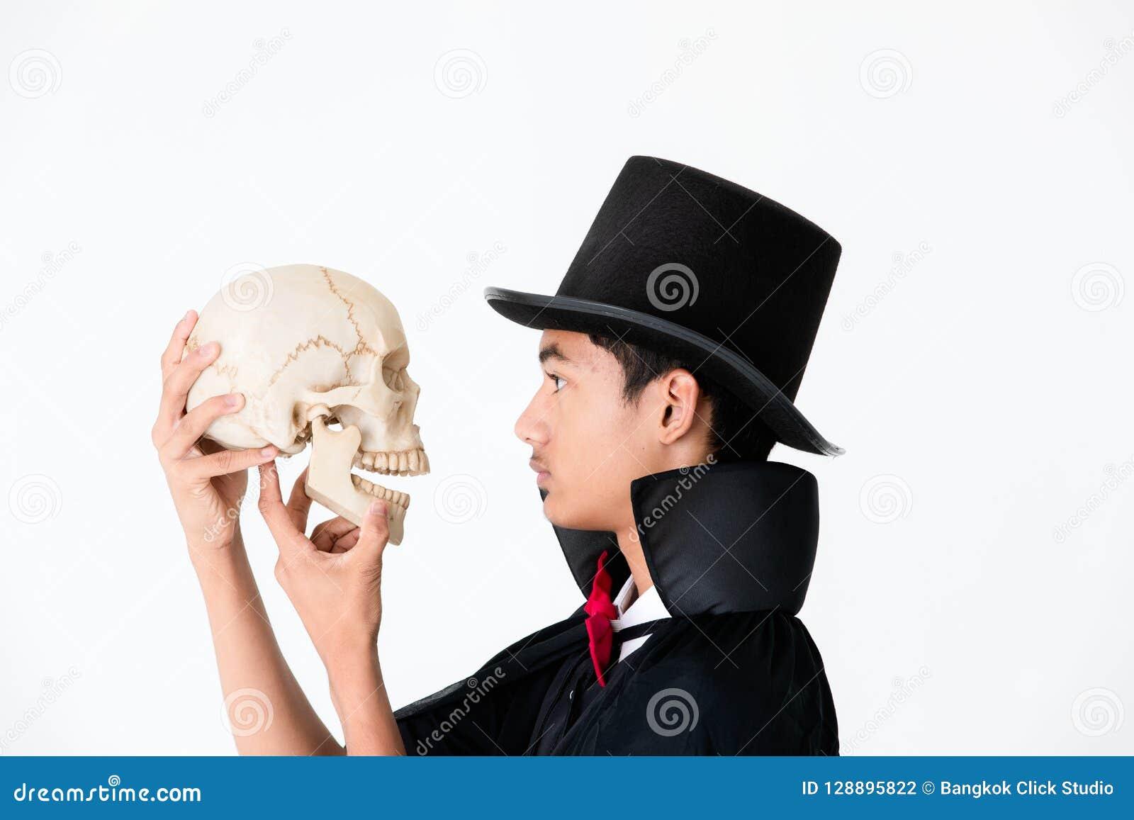 Jeune garçon asiatique dans la couverture noire et le chapeau noir se tenant et regardant