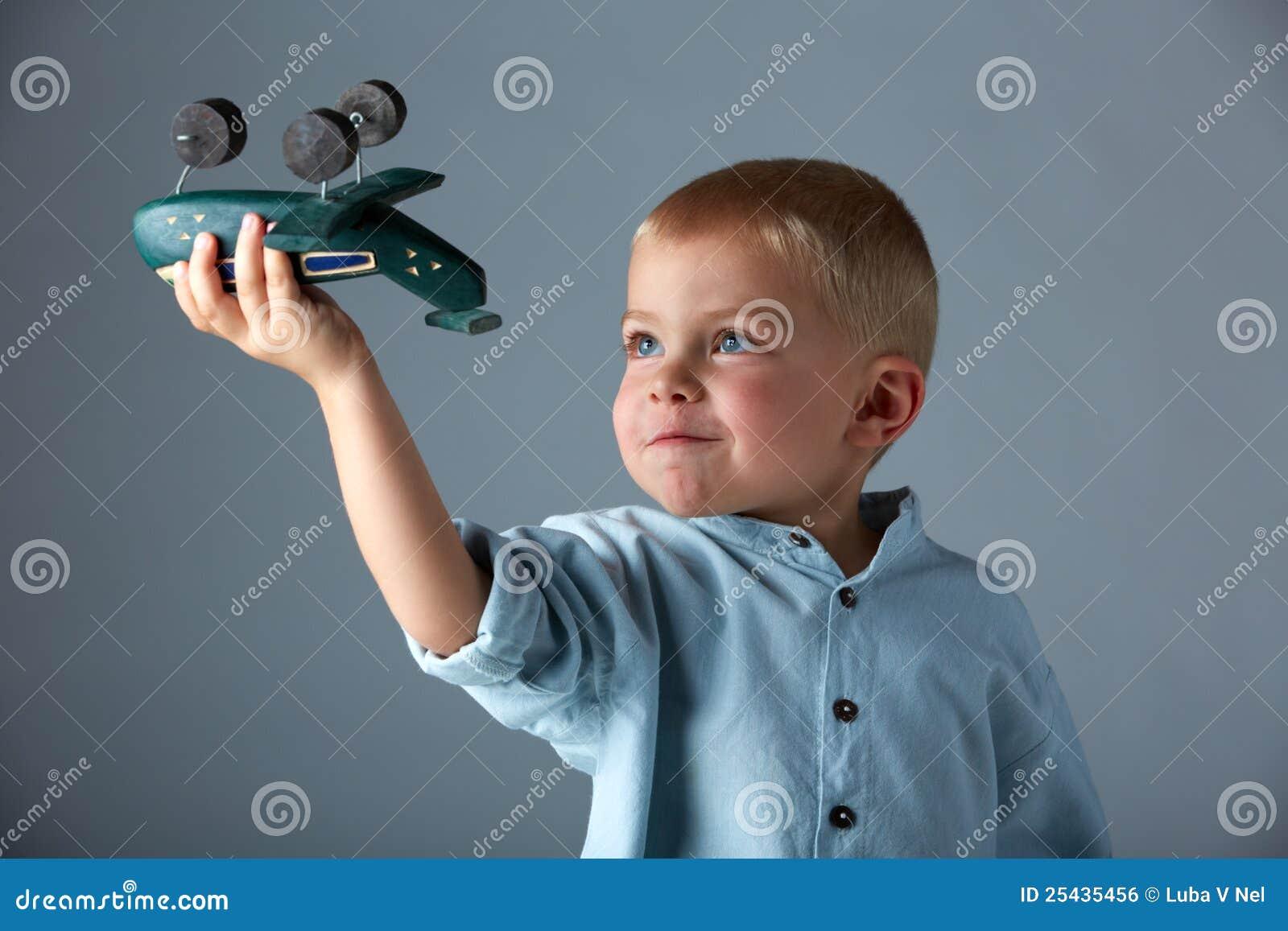 Jeune garçon avec l avion en bois