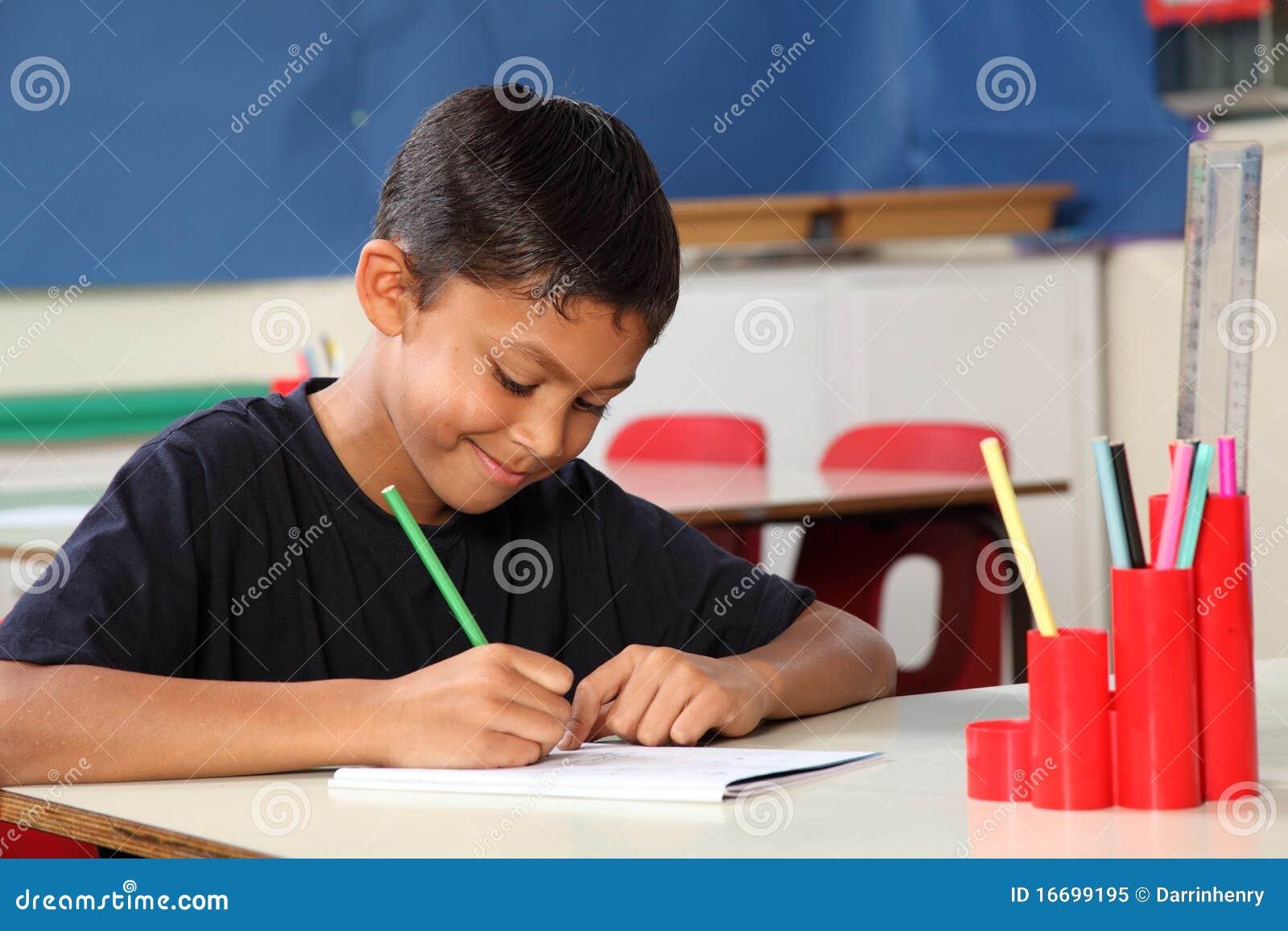 Jeune garçon d école 10 écrivant à son bureau de salle de classe