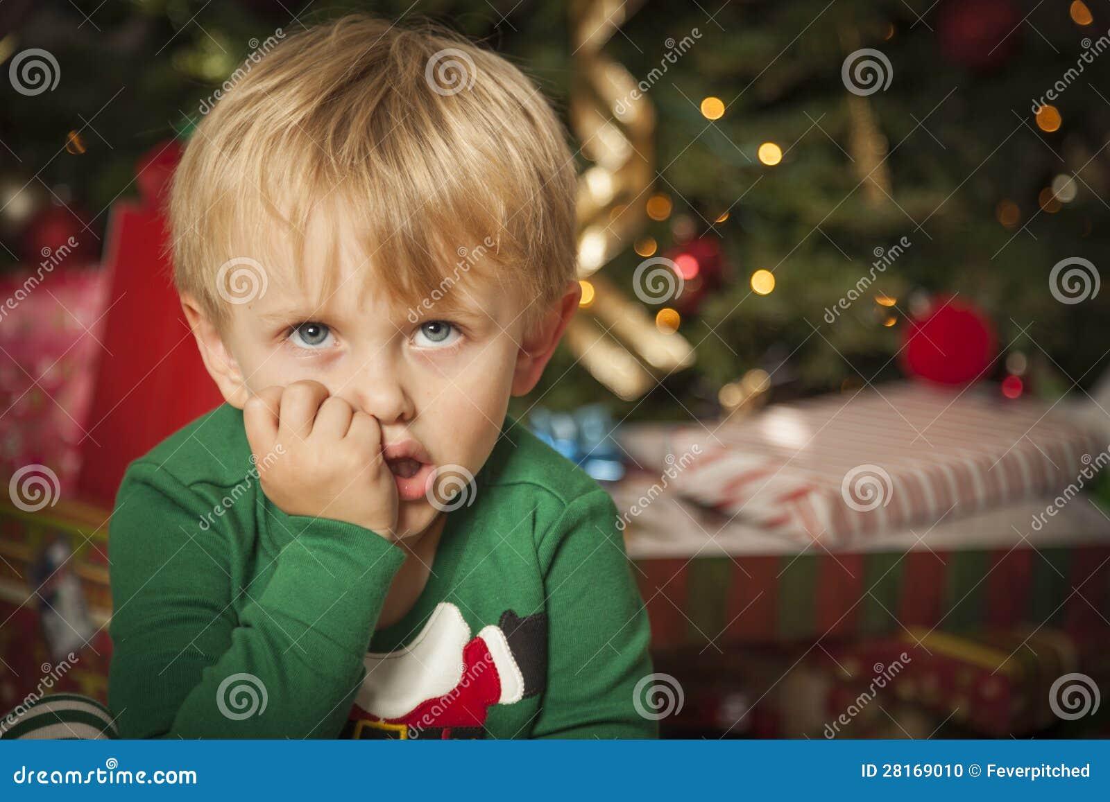 Jeune garçon grincheux s asseyant près de l arbre de Noël