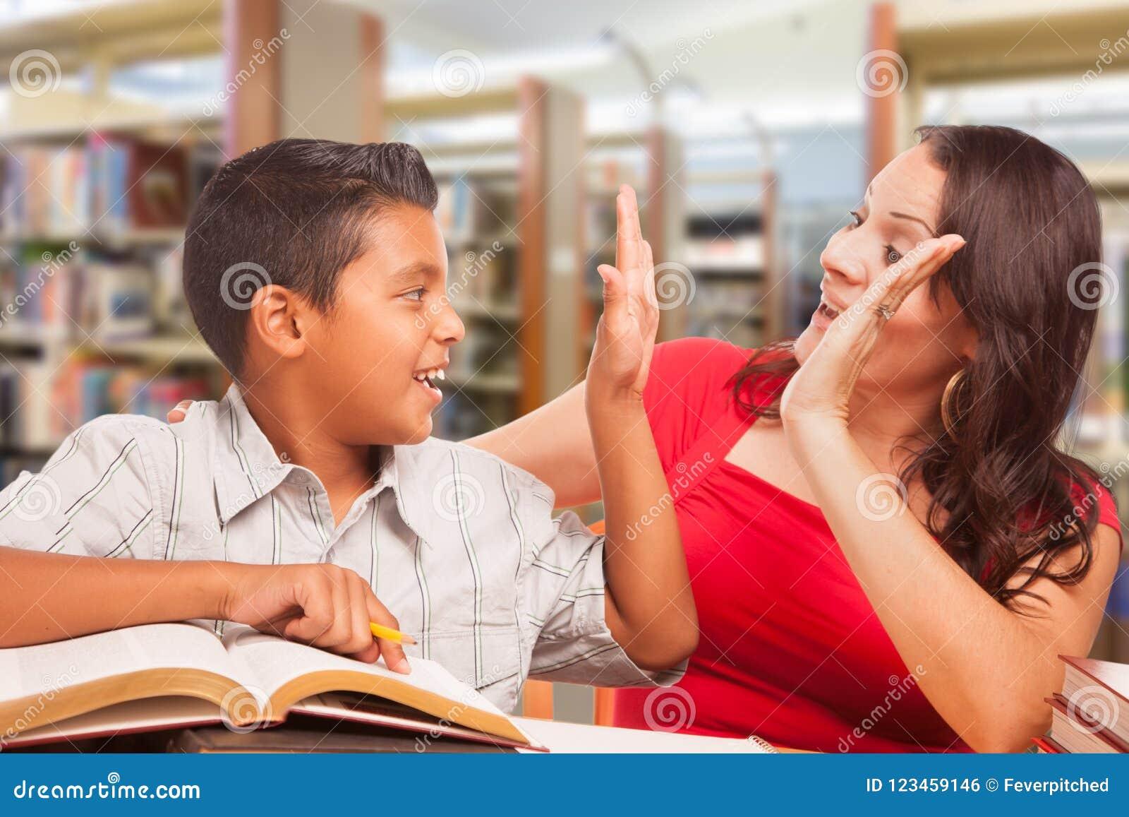 Jeune garçon hispanique et haute adulte femelle cinq étudiant