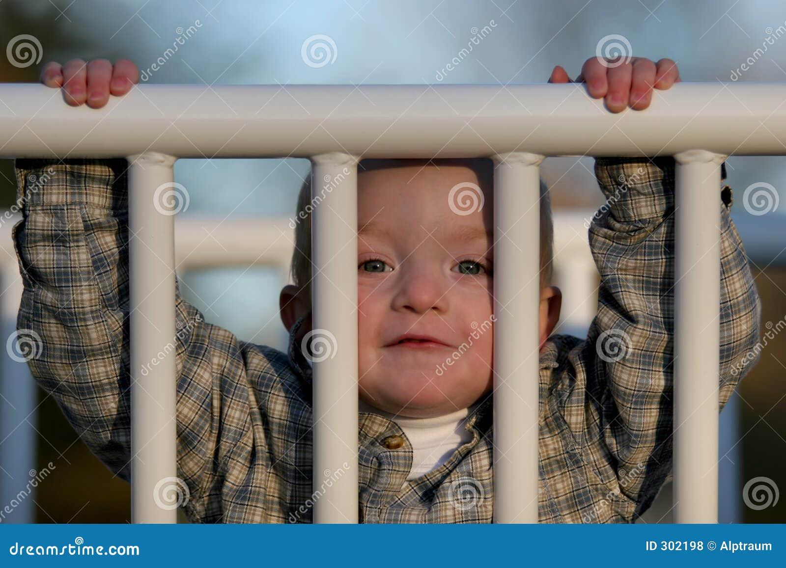 Jeune garçon mignon scrutant par la porte
