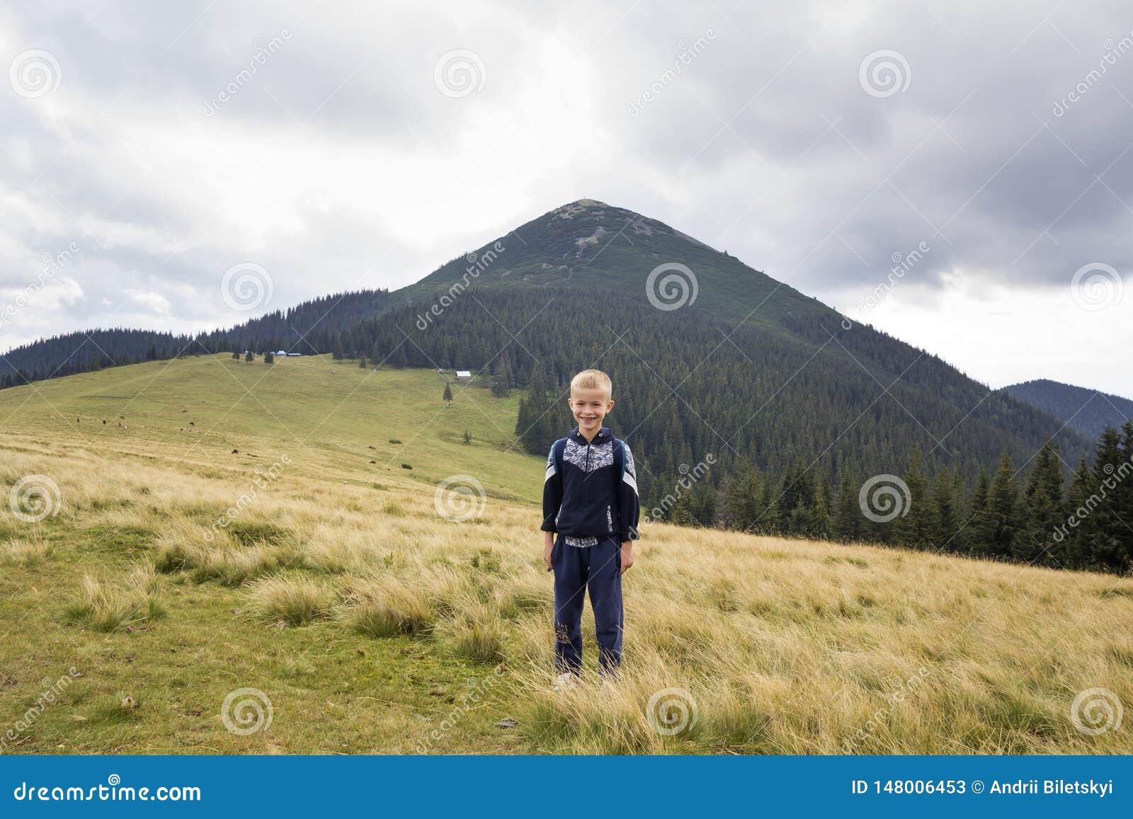Jeune gar?on de sourire heureux d enfant avec le sac ? dos se tenant en vall?e herbeuse de montagne sur le fond du paysage d ?t?,