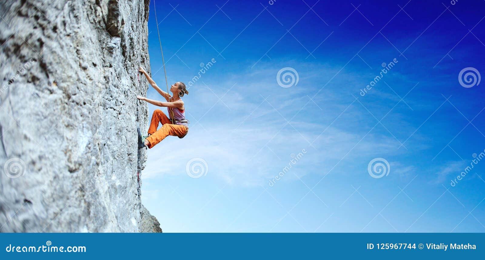 Jeune grimpeur de roche mince de femme s élevant sur la falaise