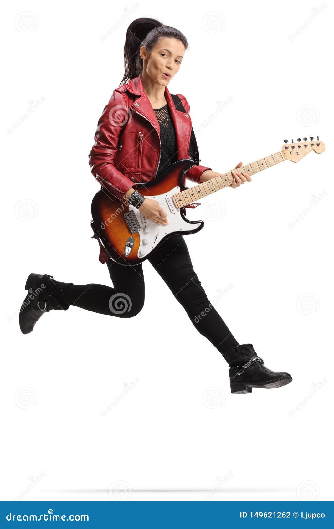 Jeune guitariste féminin jouant une guitare basse et sauter