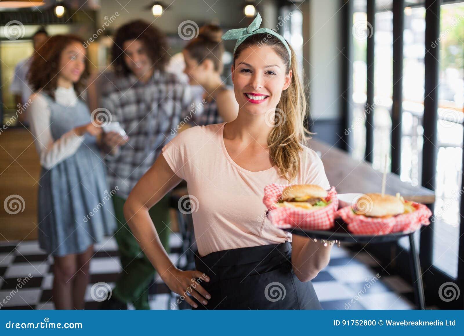 Jeune hamburger de sourire de portion de serveuse dans le restaurant