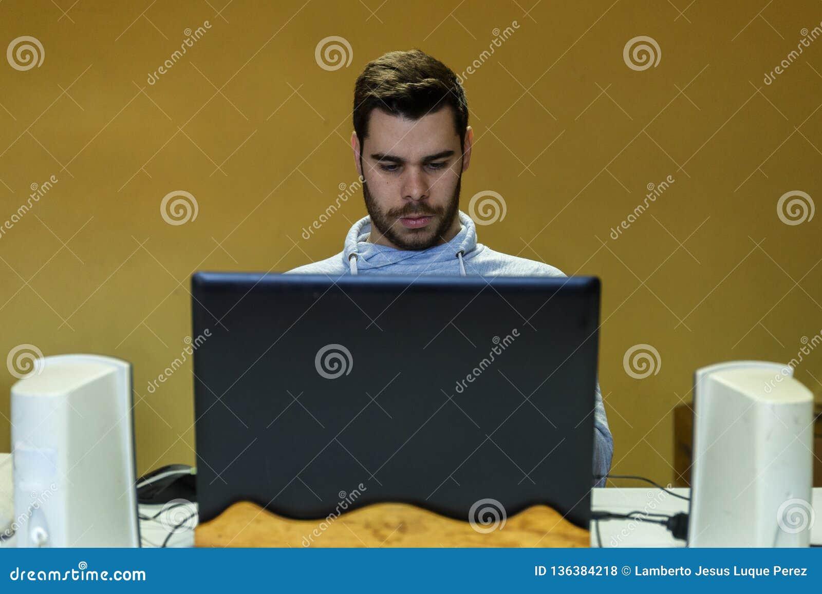 Jeune homme à l aide de son mobile, comprimé, ordinateur portable et écouteurs