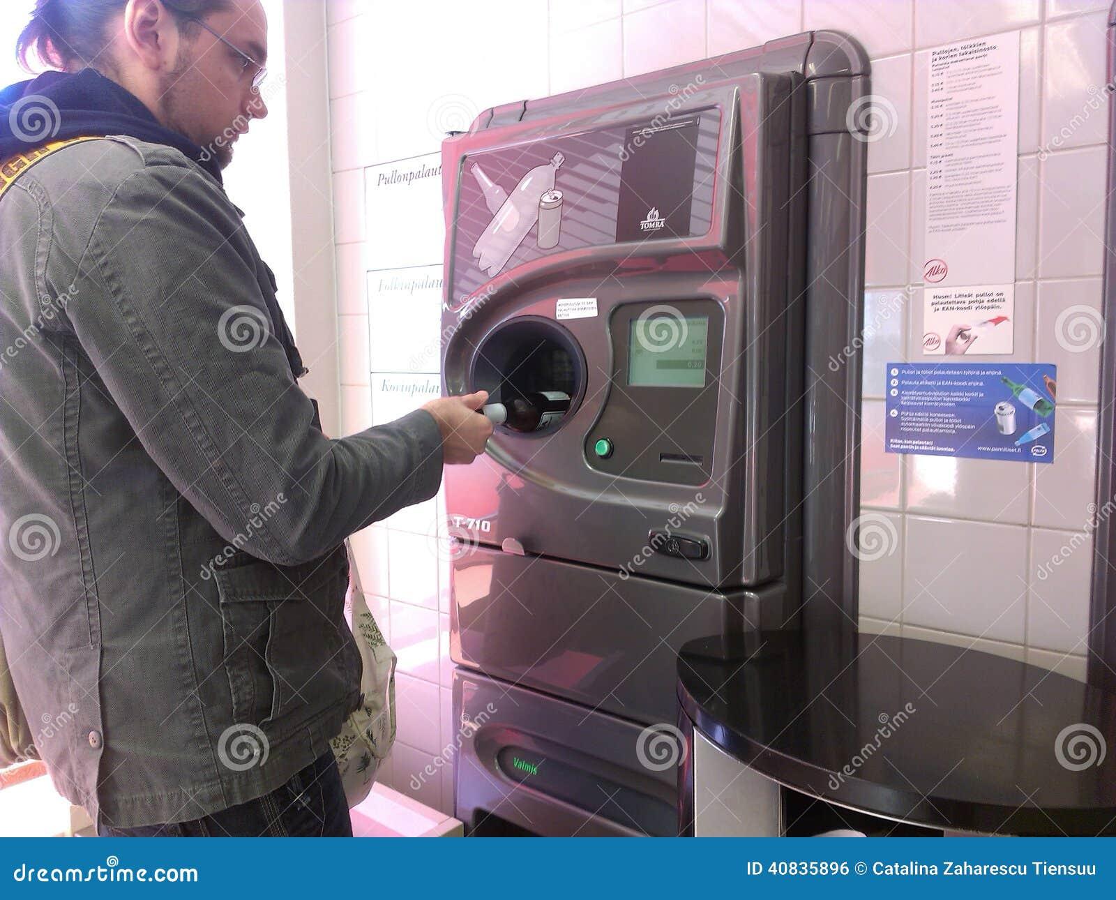 Jeune homme à l aide du distributeur automatique inverse