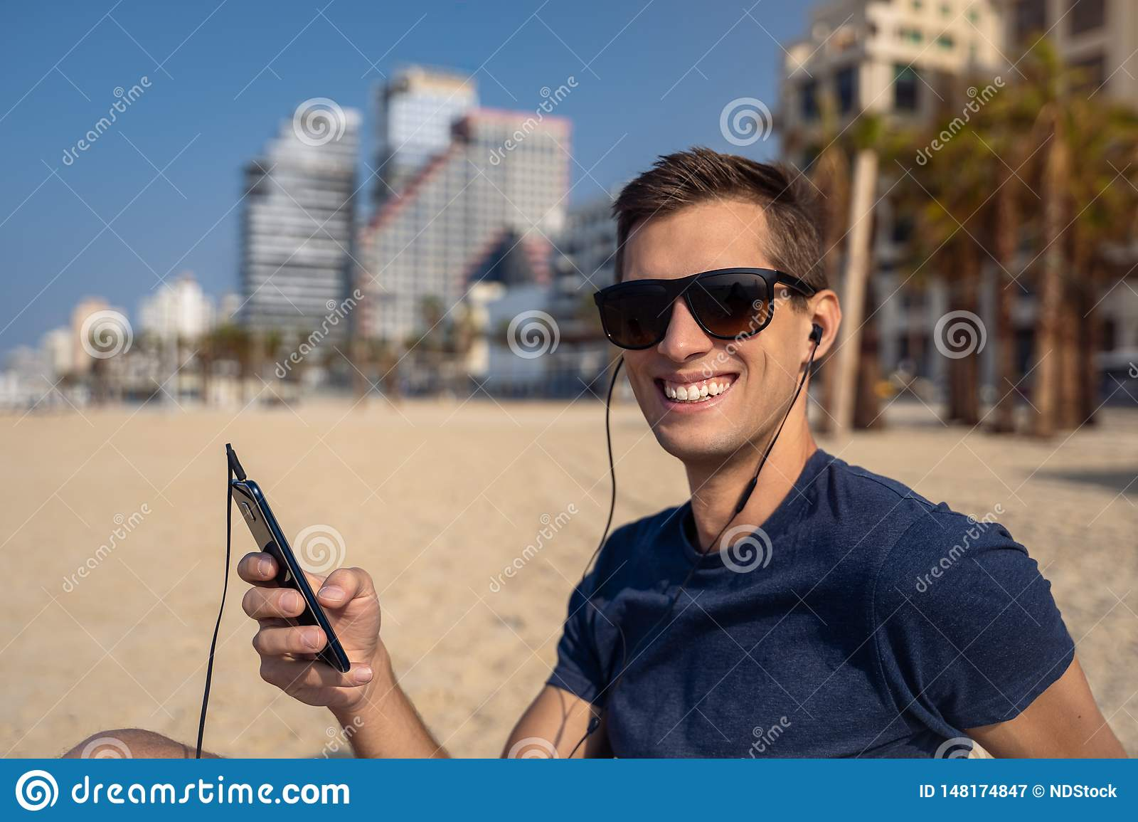Jeune homme à l aide du téléphone avec le casque sur la plage Horizon de ville ? l arri?re-plan