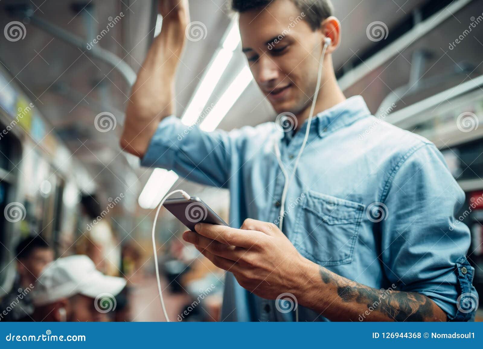 Jeune homme à l aide du téléphone dans le souterrain, dépendance