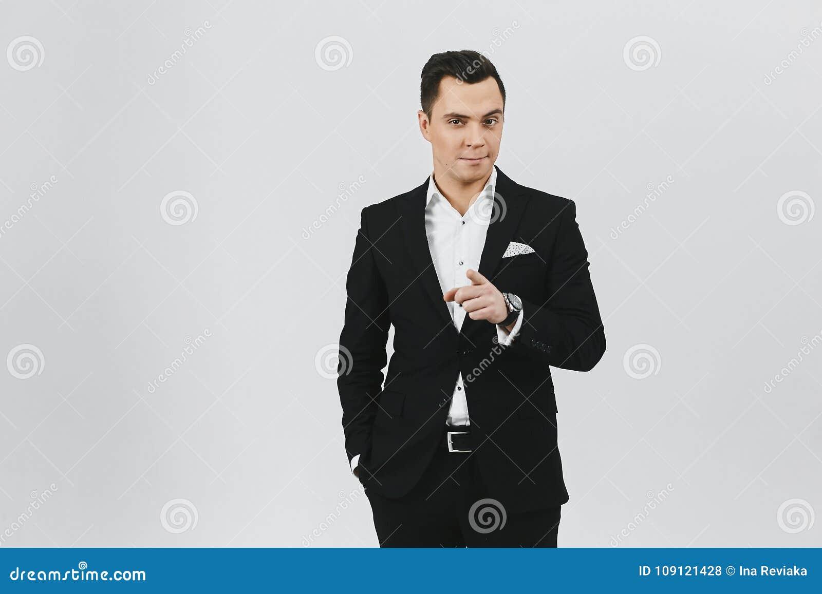 Jeune homme à la mode élégant de brune dans une chemise blanche et costume  noir sur le fond blanc 9641d2c0dc0