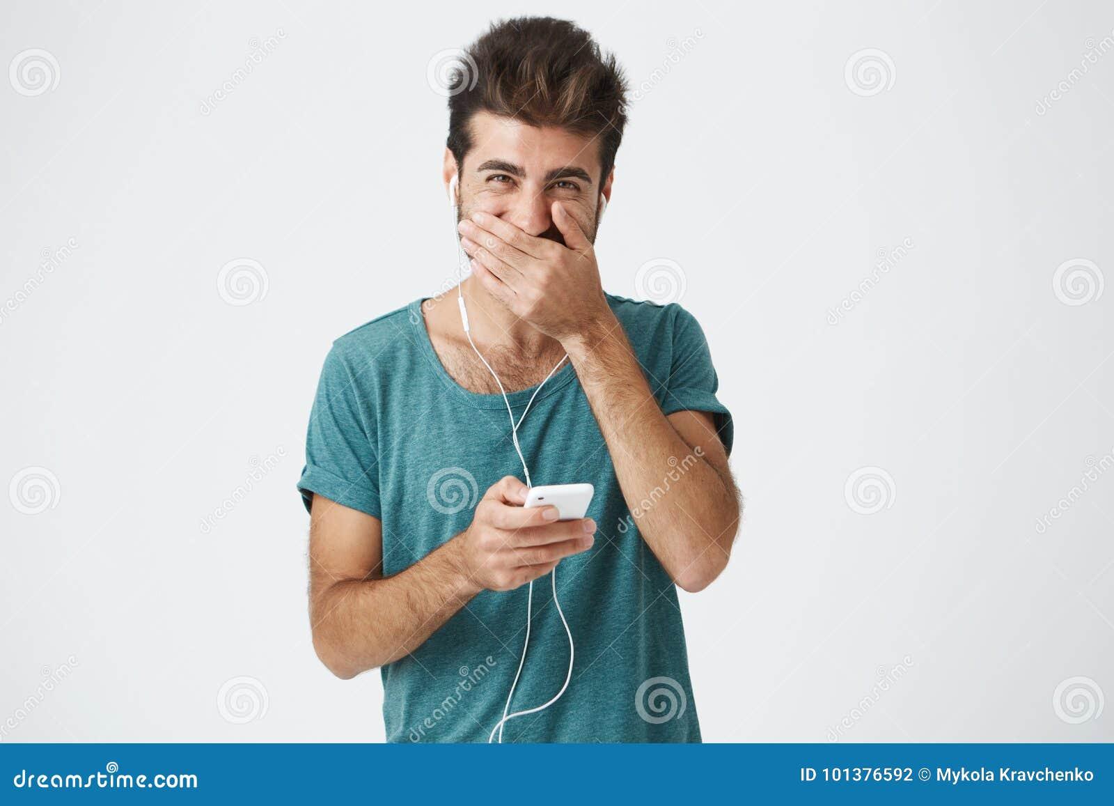 Jeune homme élégant hispanique heureux utilisant le T-shirt bleu à la mode, souriant et regardant à l appareil-photo, couvrant la