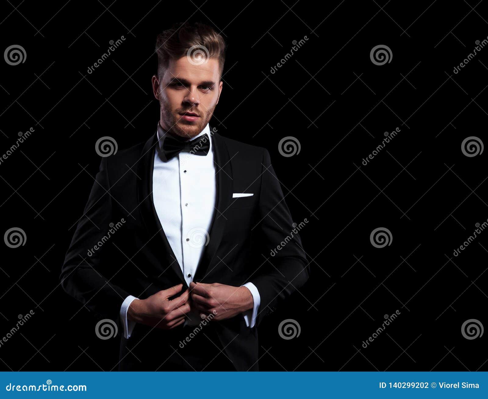 Jeune homme élégant tenant son bouton de manteau