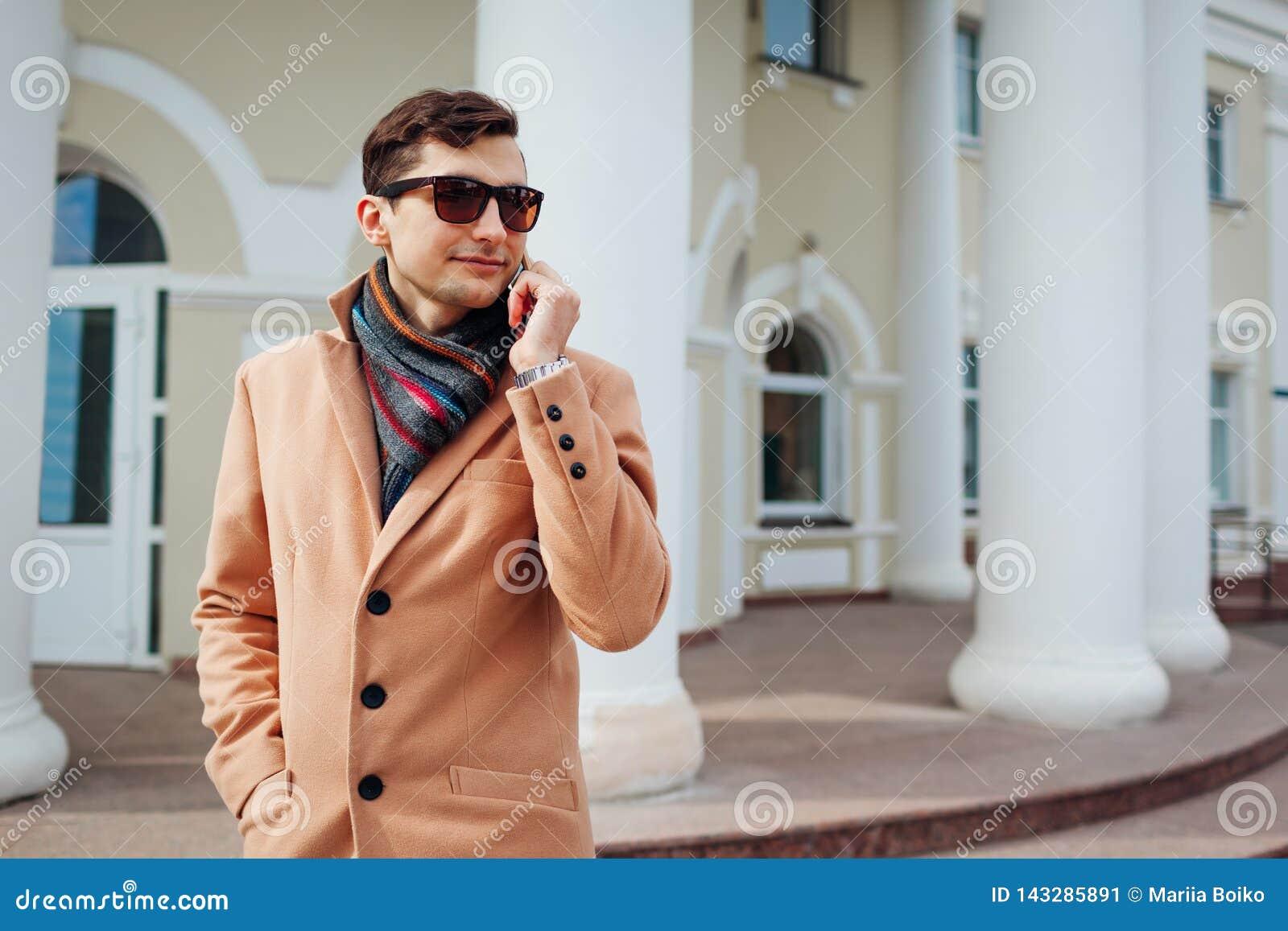 Jeune homme élégant utilisant le smartphone dans la ville Type beau utilisant les vêtements et les accessoires classiques Mode de