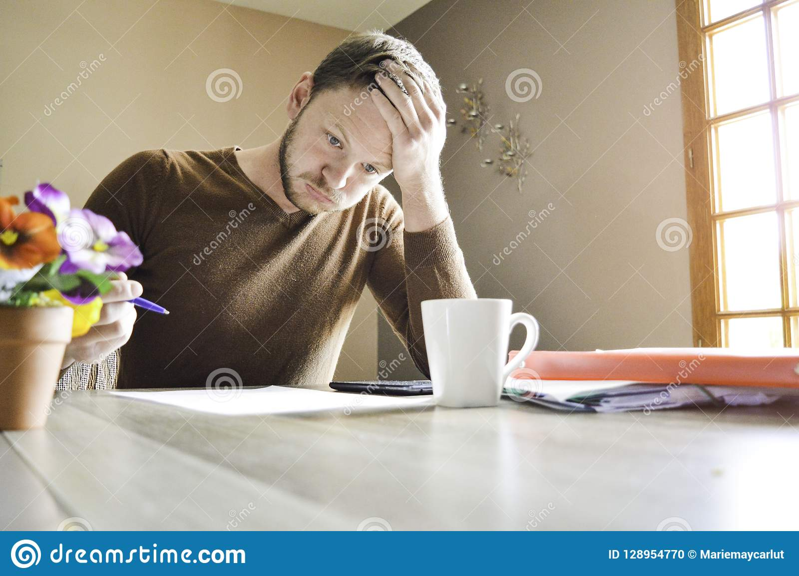 Jeune homme actif tenant sa tête travaillant dur sur des écritures au bureau