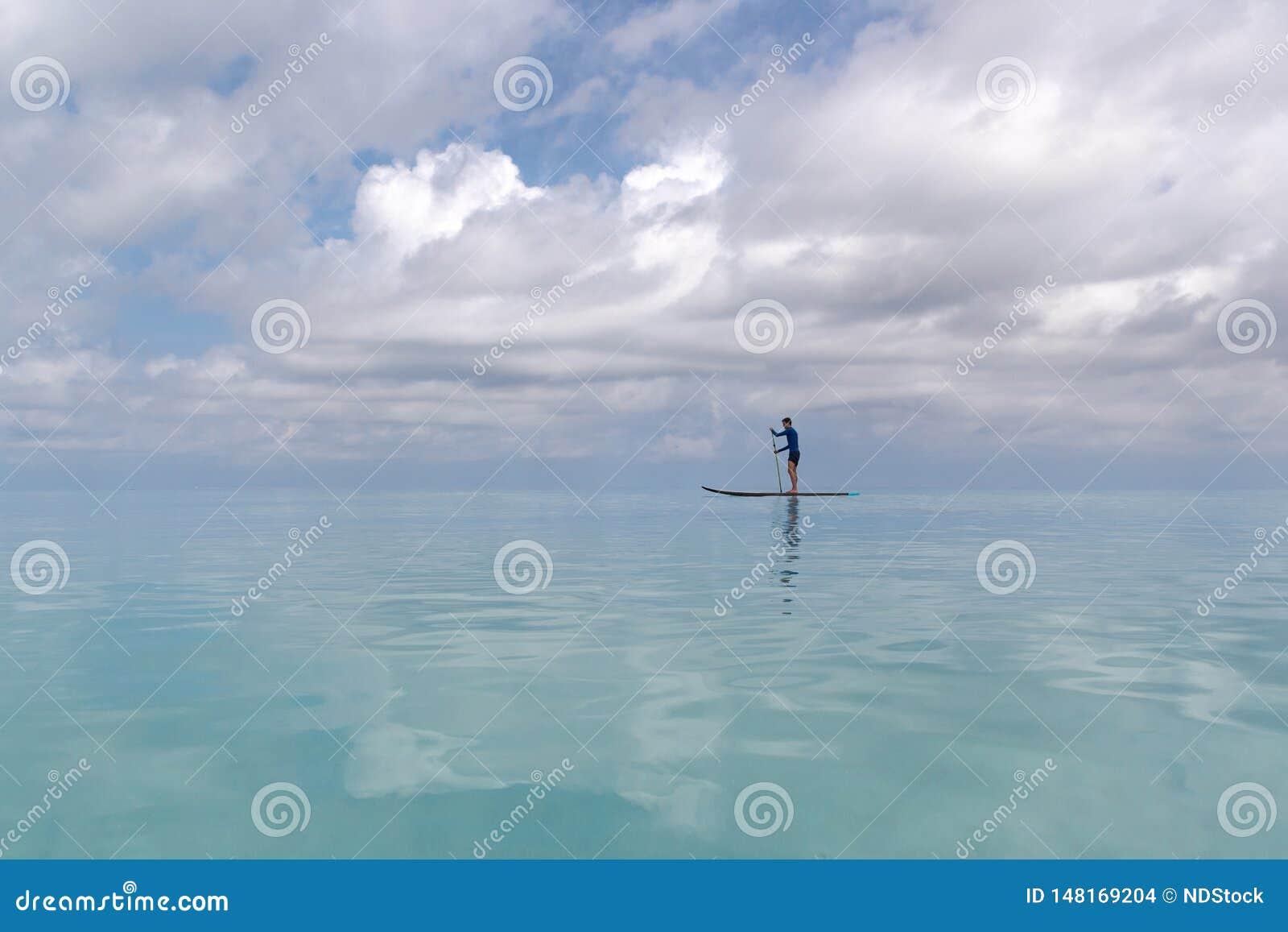Jeune homme adulte avec de support la palette dans l eau bleue claire