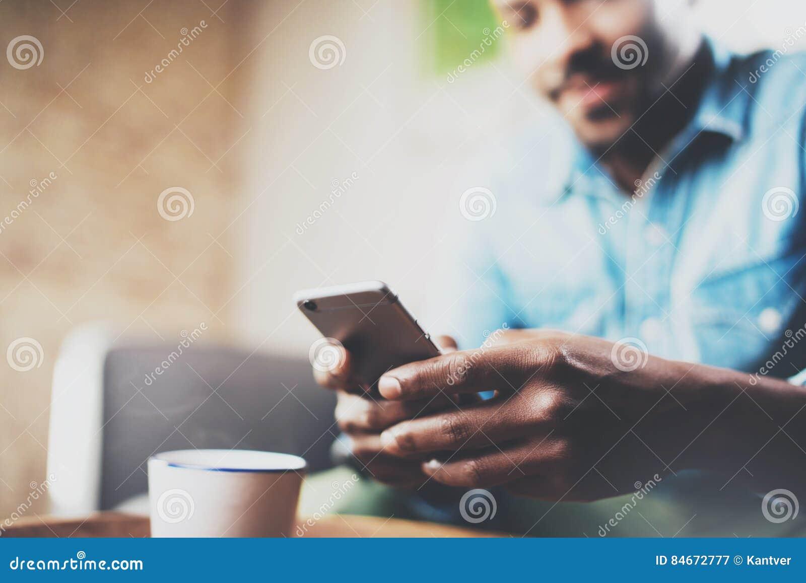 Jeune homme africain barbu à l aide du smartphone tout en se reposant sur le sofa à la maison Personnes de concept travaillant av