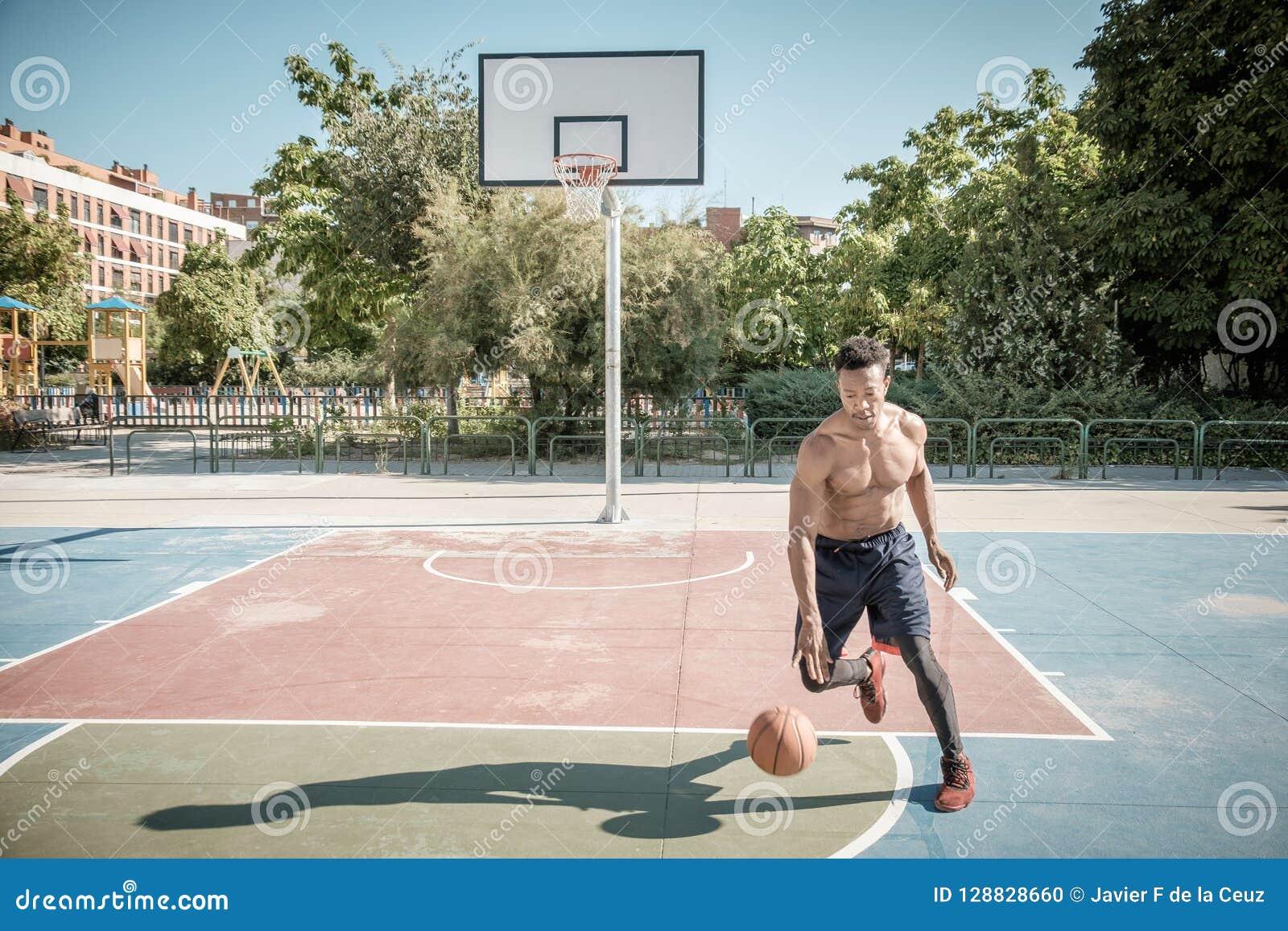 Jeune homme afro-américain jouant le basket-ball de rue en parc