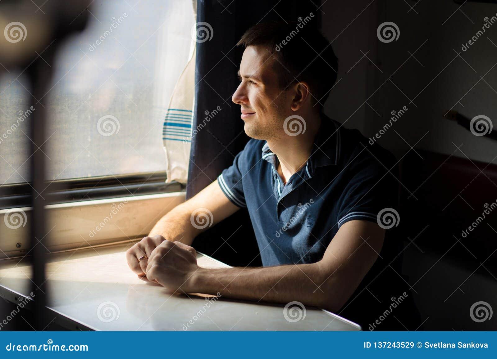 Jeune homme appréciant le voyage de train - laissant sa voiture à la maison, regarde hors de la fenêtre, a le temps pour admirer