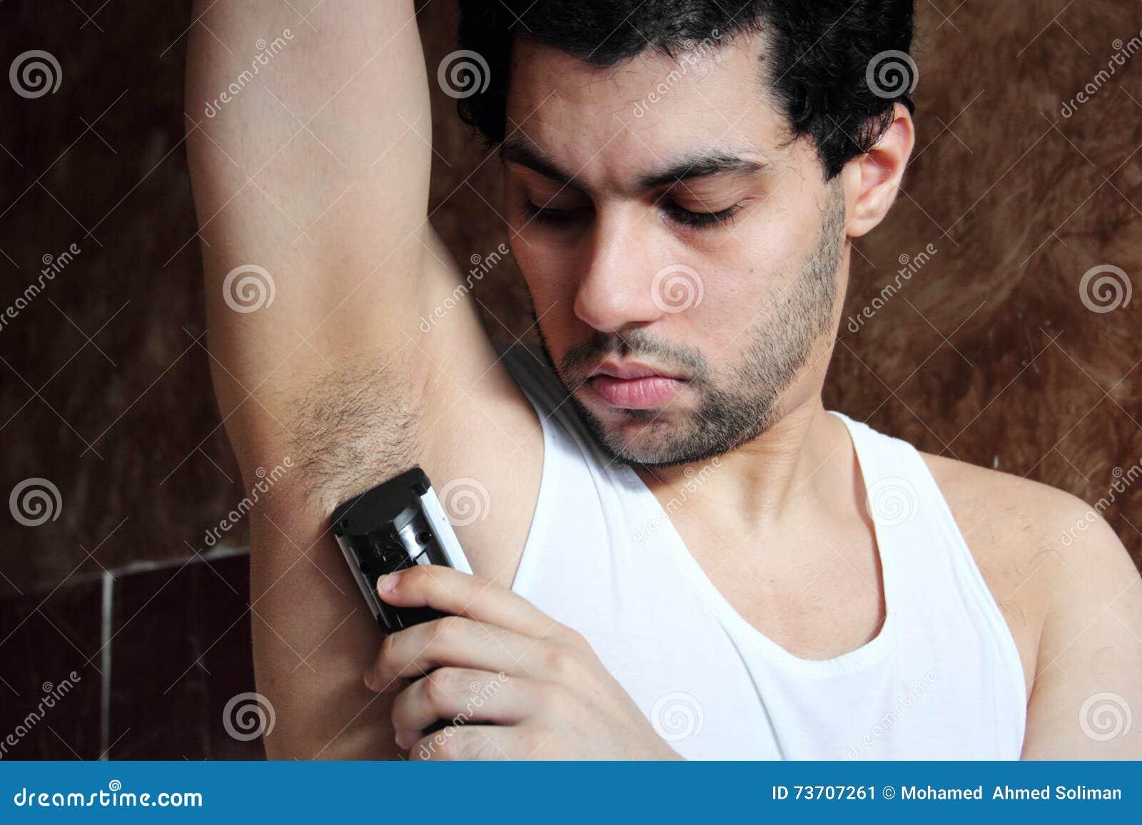 jeune homme arabe rasant des cheveux d 39 aisselle avec la tondeuse image stock image du cheveu. Black Bedroom Furniture Sets. Home Design Ideas