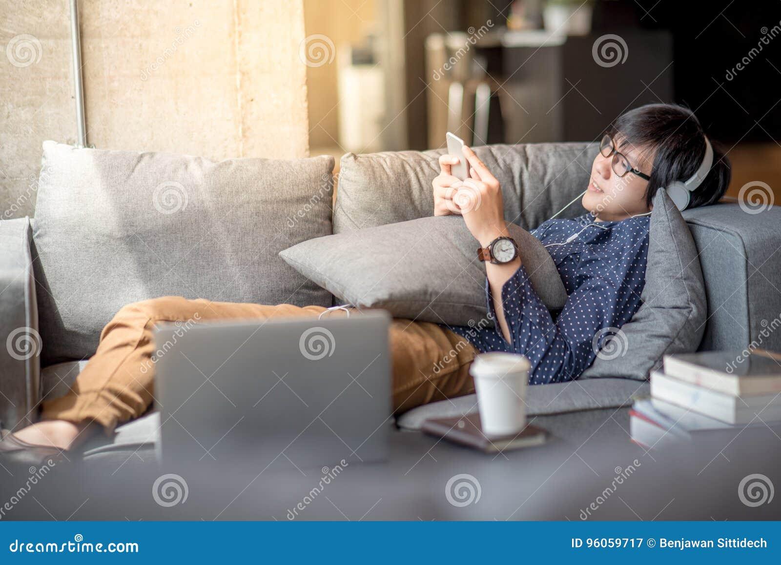 Jeune homme asiatique à l aide du smartphone détendant sur le sofa