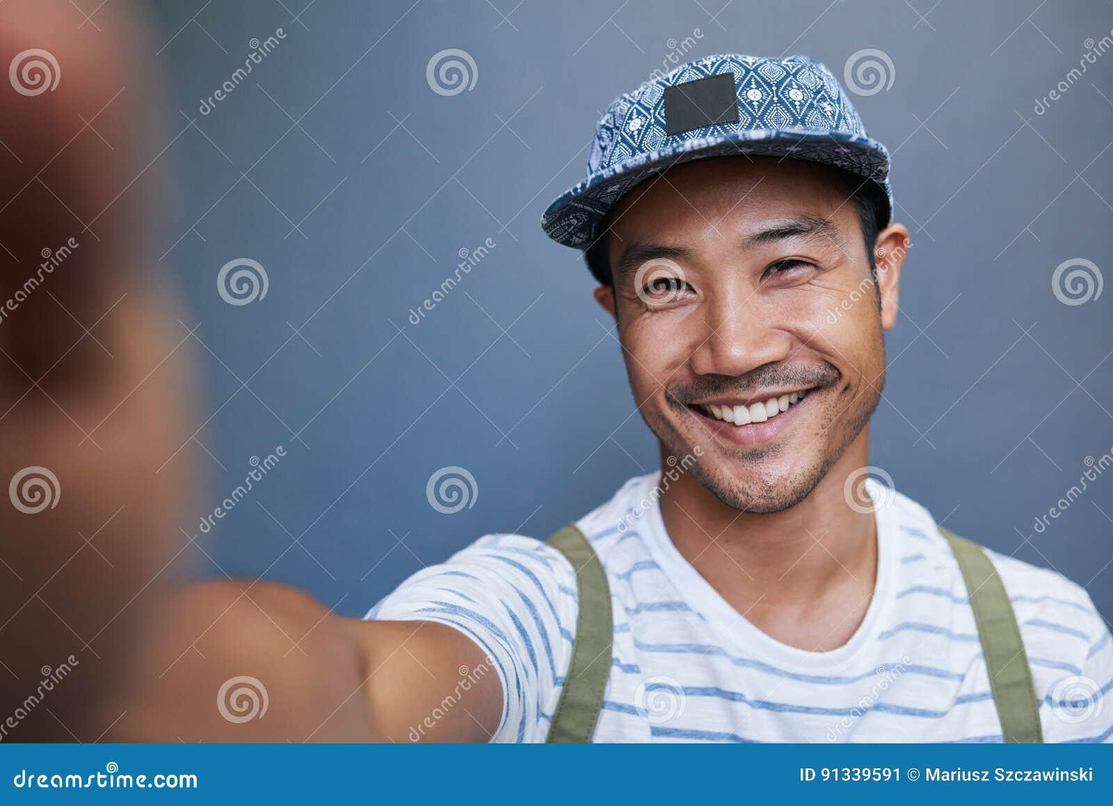 Jeune homme asiatique élégant prenant un selfie dehors