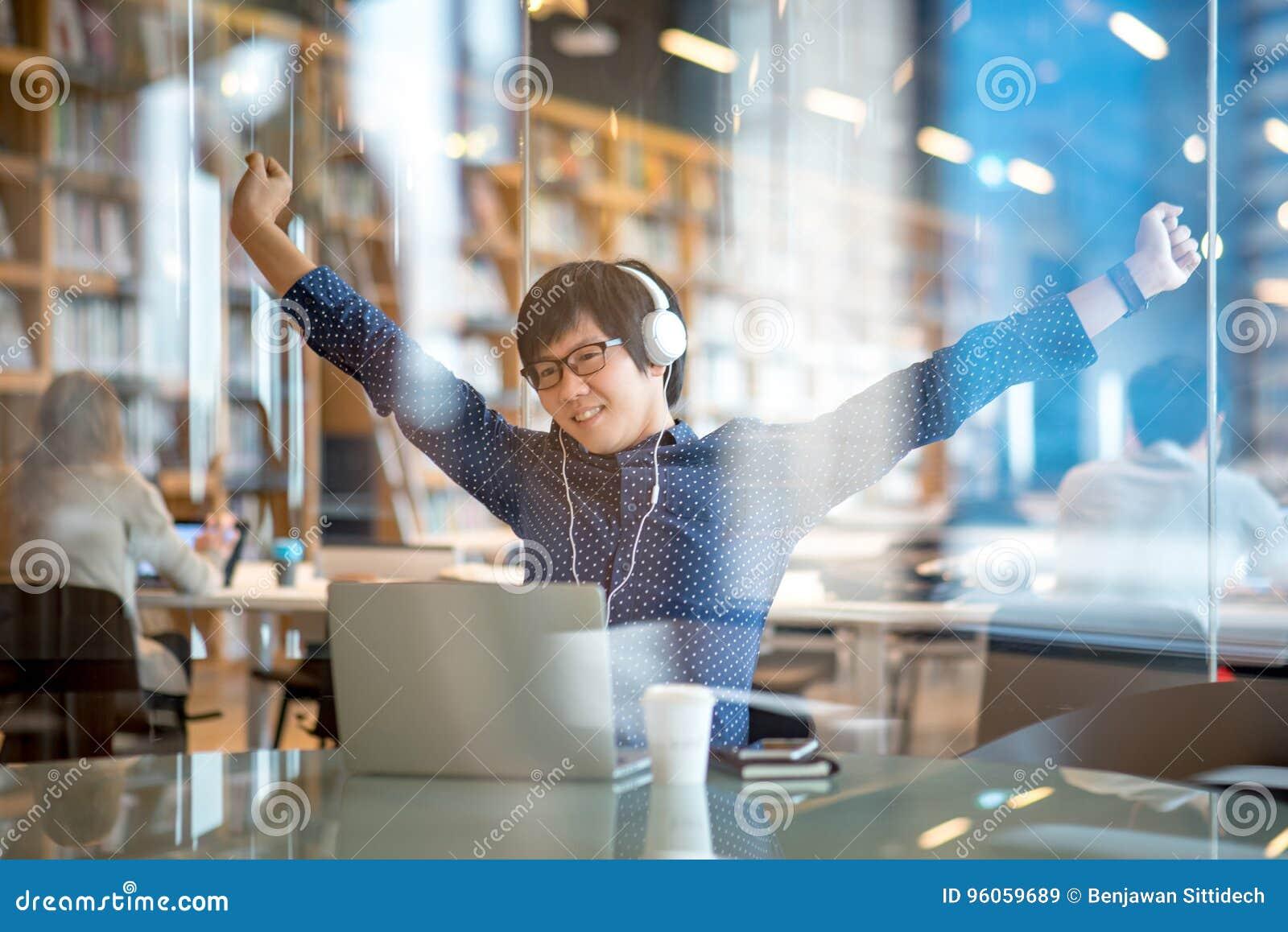 Jeune homme asiatique étirant son bras dans la bibliothèque