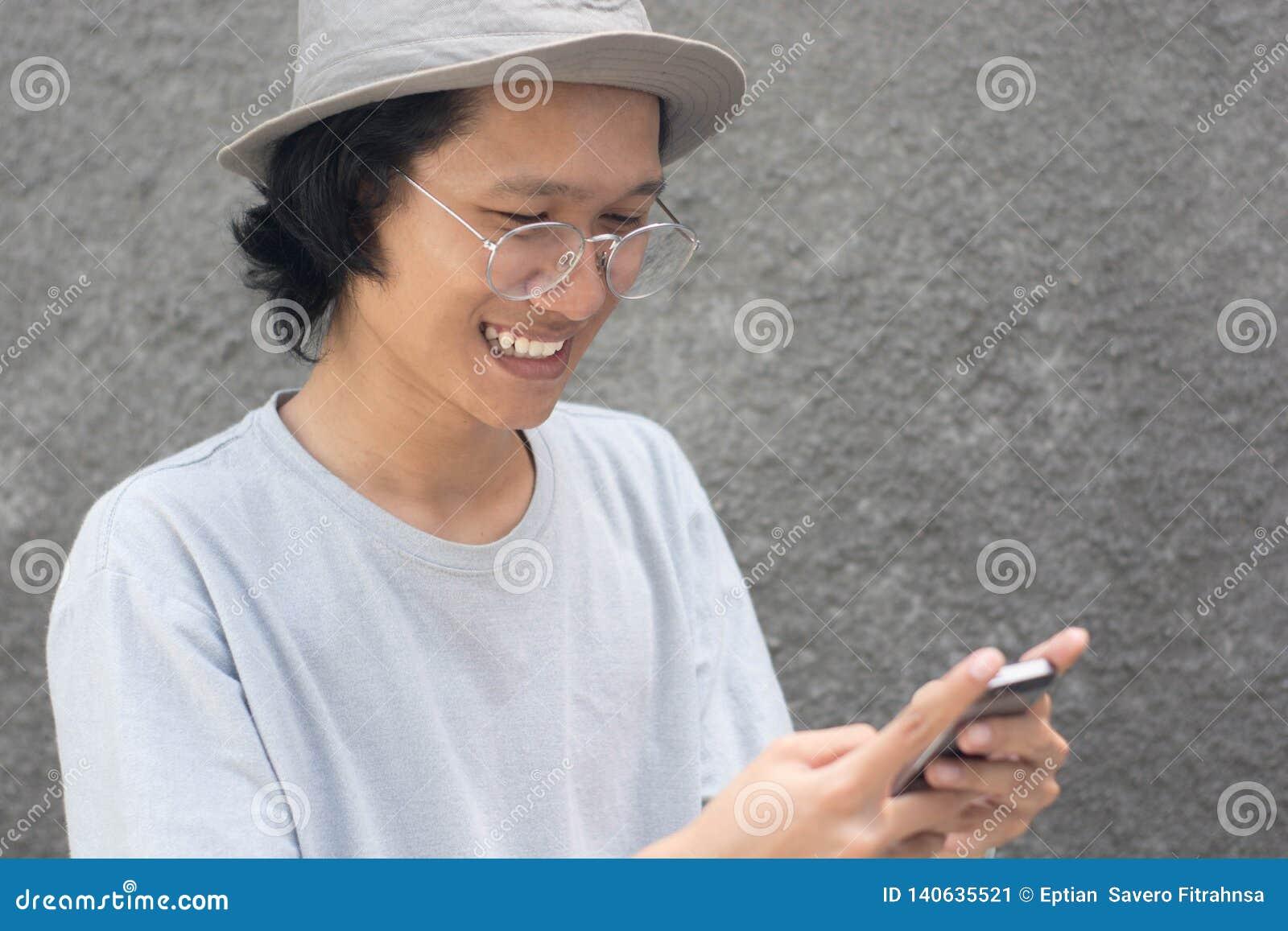 Jeune homme asiatique attirant avec le chapeau et les verres utilisant le smarphone et le sourire