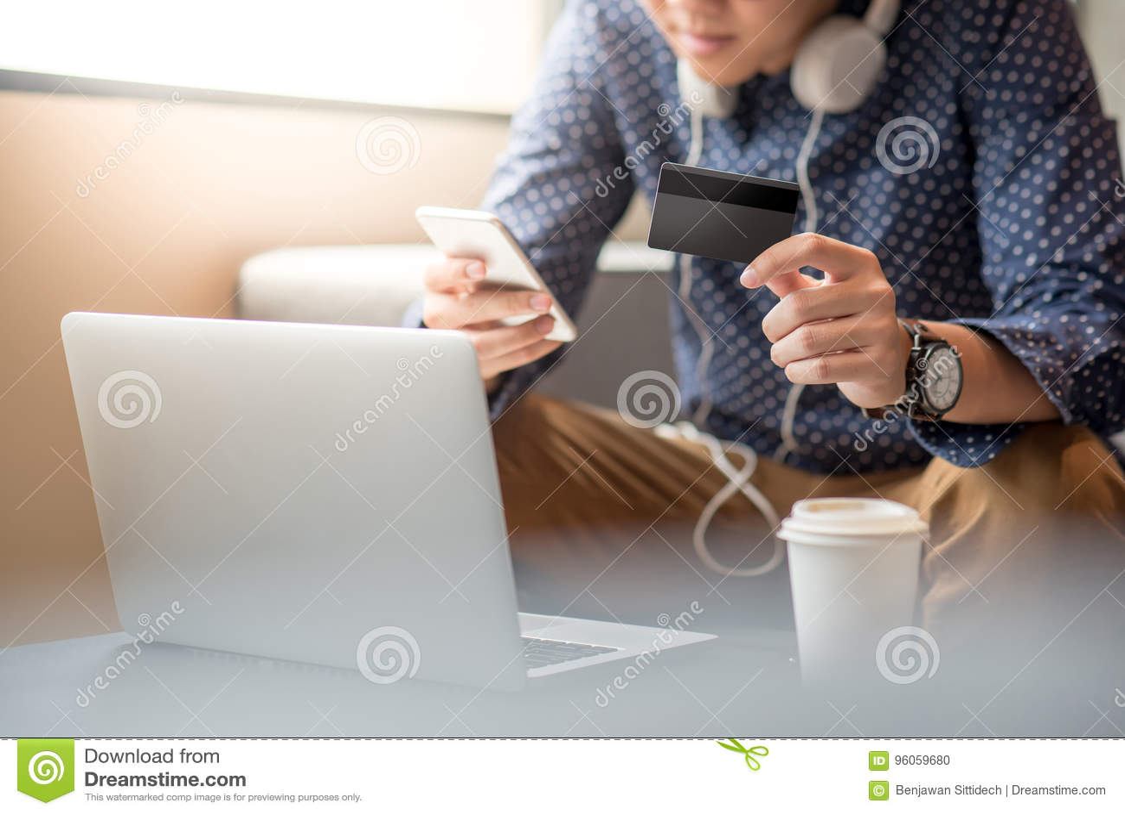 Jeune homme asiatique employant la carte de crédit pour des achats en ligne