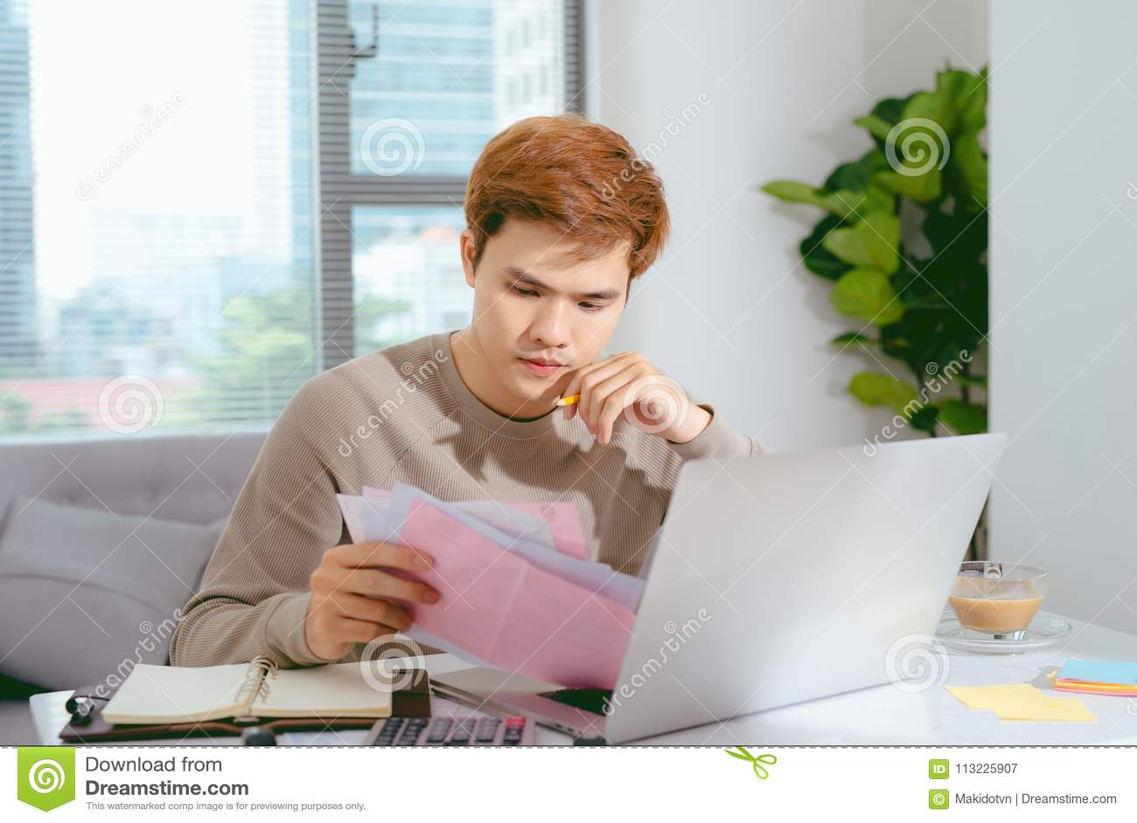 Jeune homme asiatique payant ses factures à la maison dans le salon